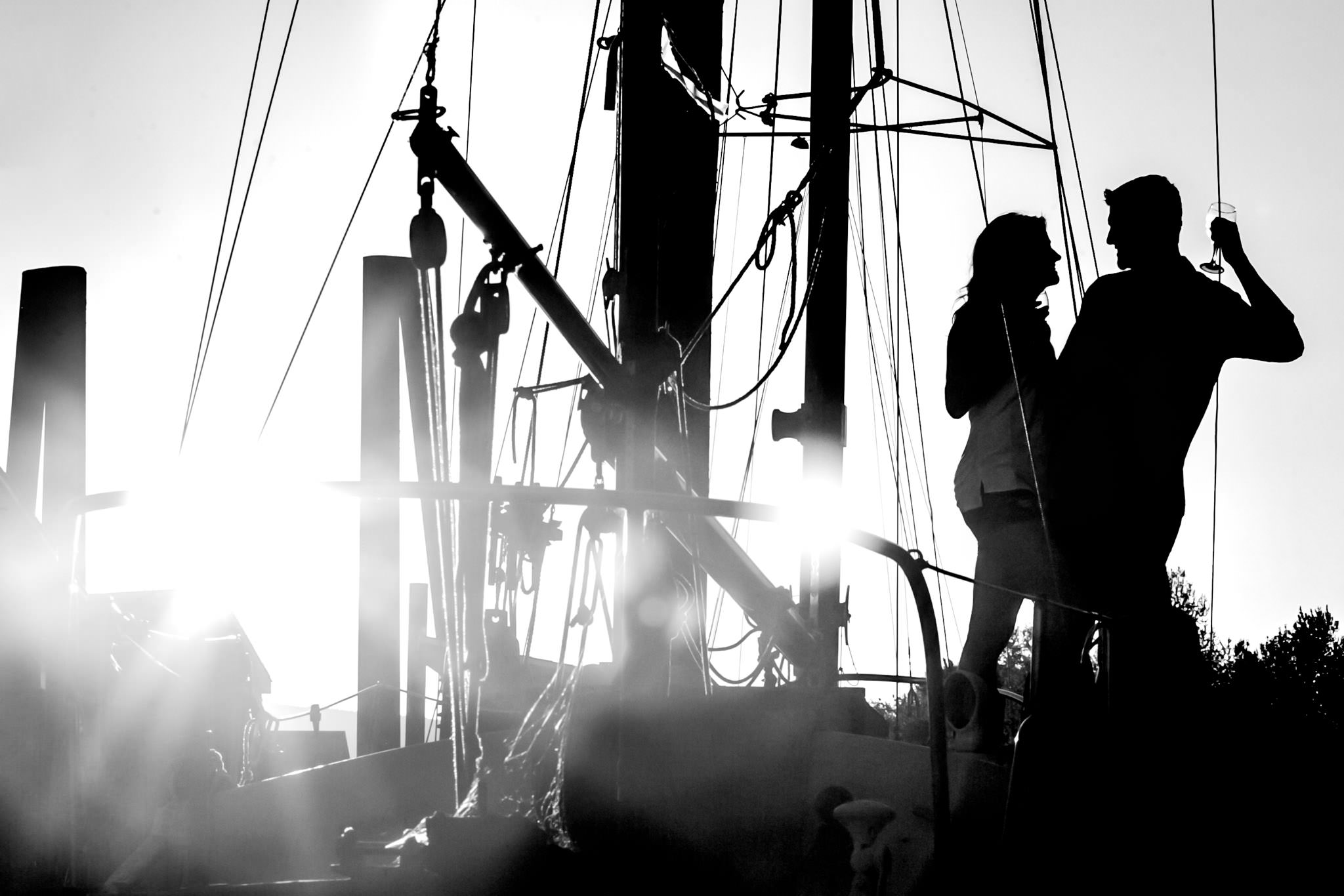 Engagement portrait of couple on sail boat at sunset with silhouettes