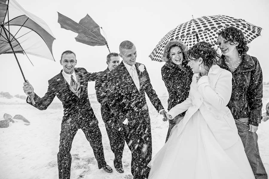 Bridal party walking in snow storm laughing atop Timberline Lodge outside Silcox Hut