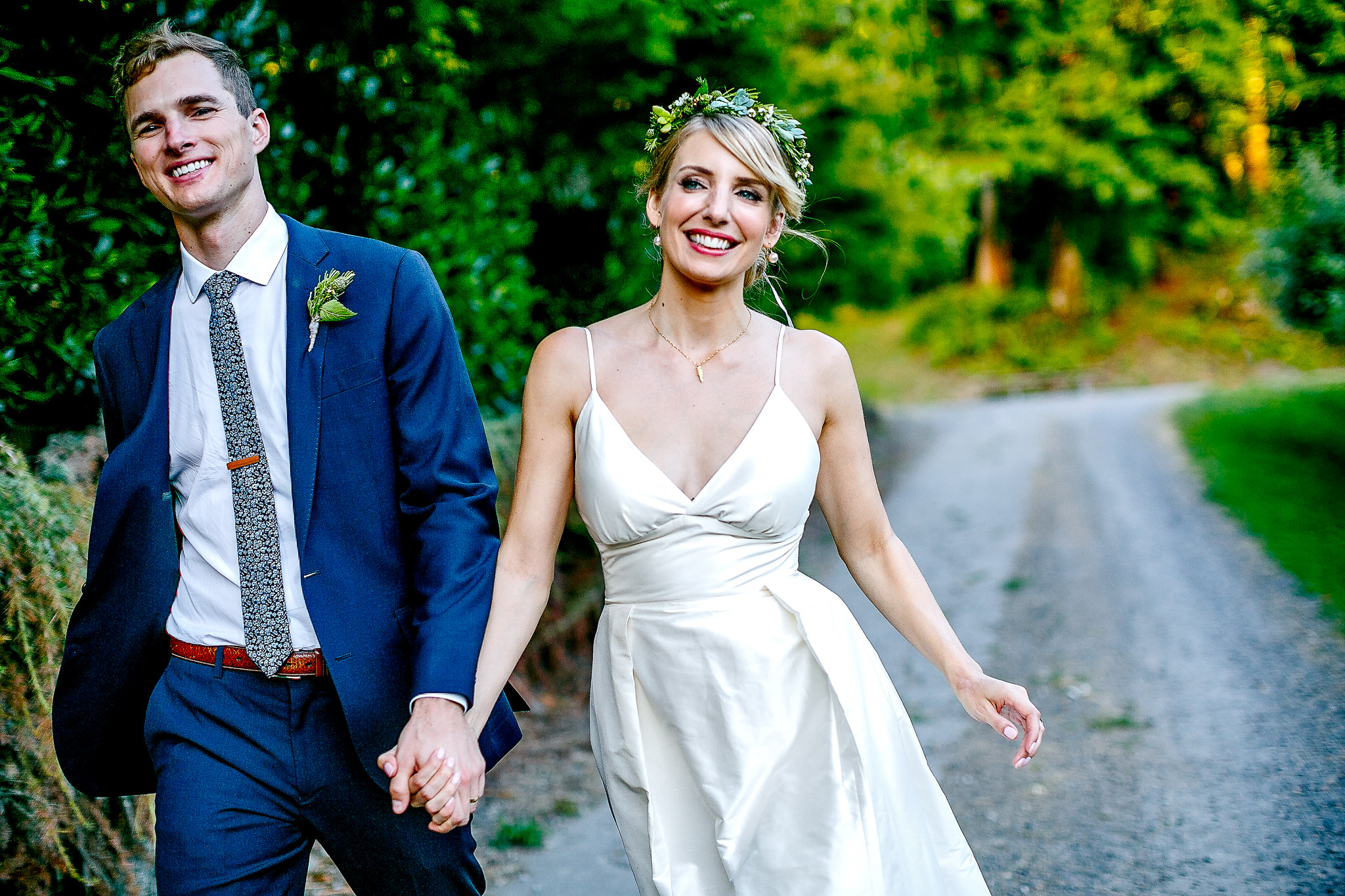 Gorgeous bride with flower crown and groom walking and laughing down gravel road in forest Camp De Angelos