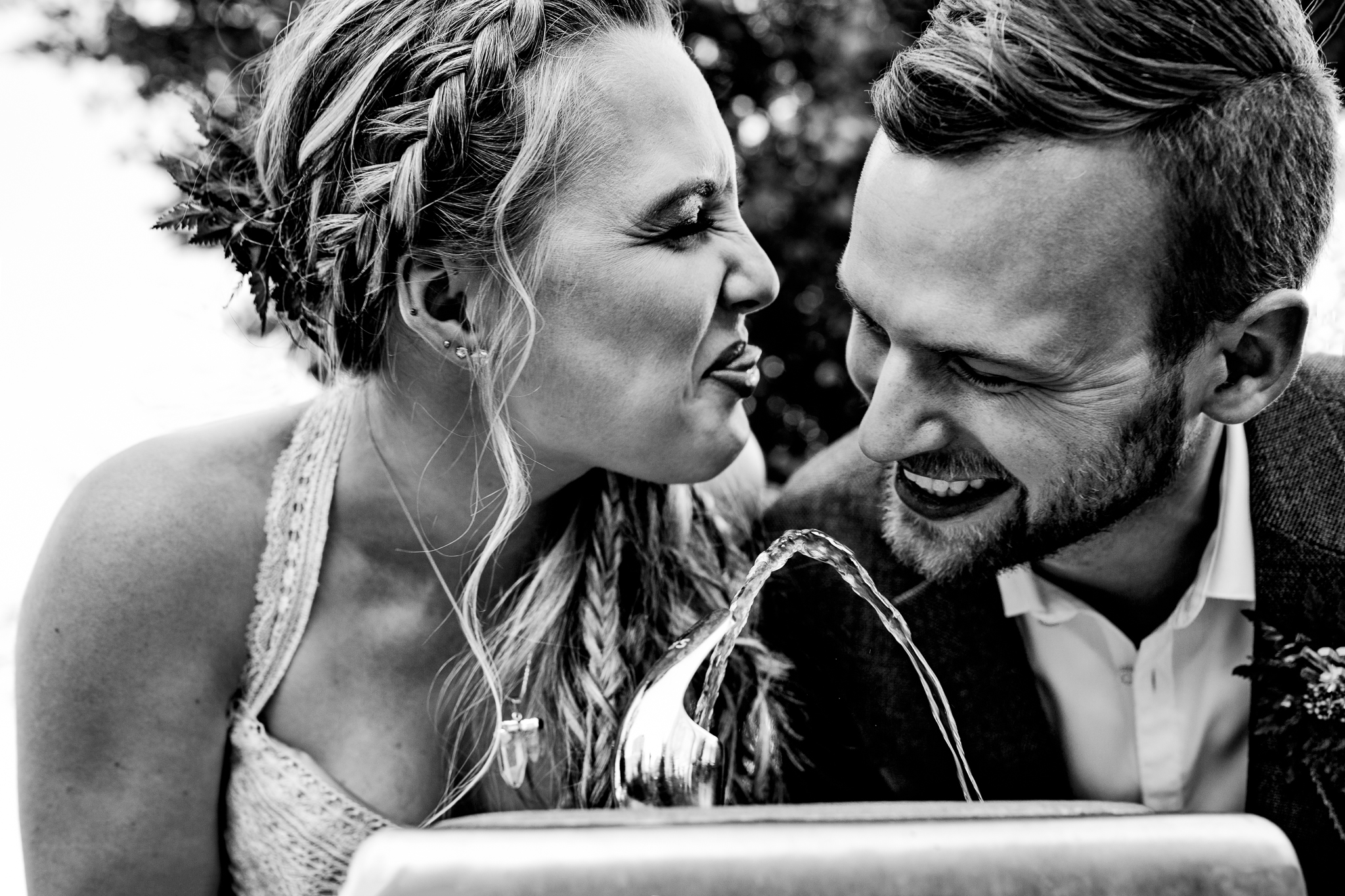 Bride and Groom playing around water fountain