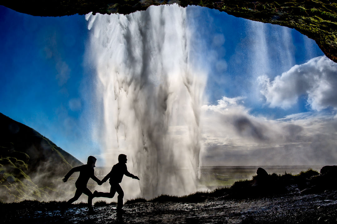 Engagement Shoot Iceland with couple running through waterfall