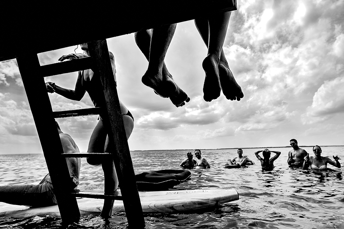 bride and groom feet hanging over dock with bridal party in water