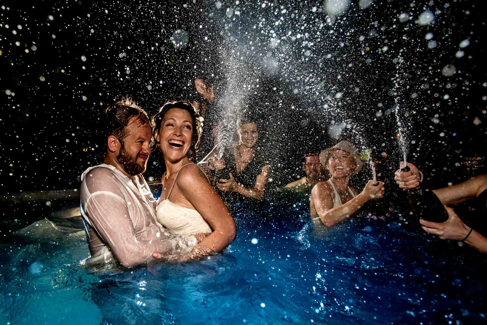 Champagne toast surprise for Bride and Groom exploding everywhere in air in pool with everyone soaking wet