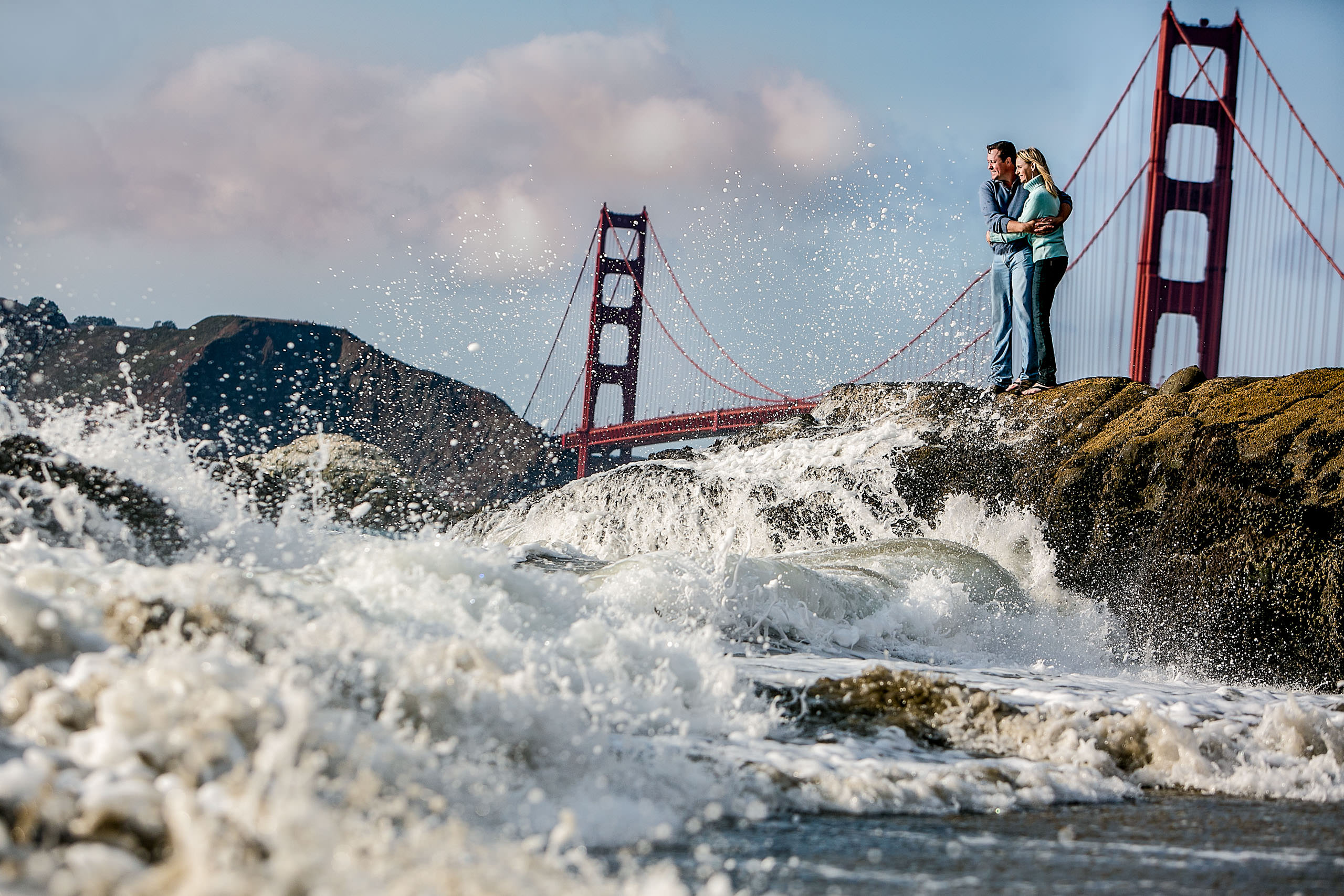 Creative engagement portrait with crashing water near San Francisco Bridge