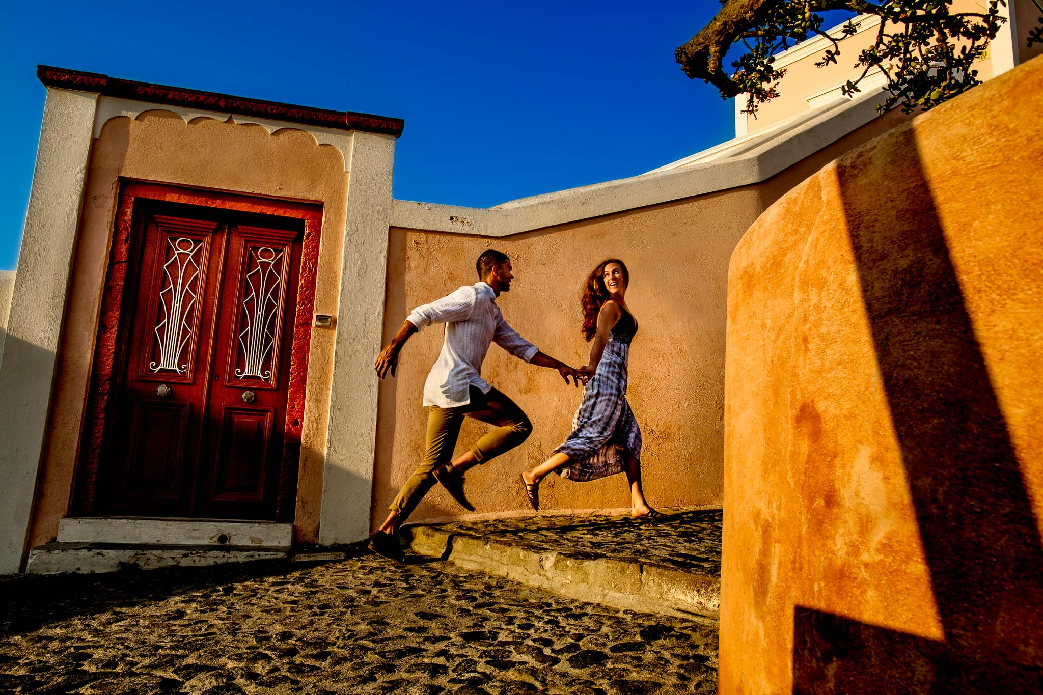Engagement photo of couple running through streets on Santorini Greece in golden sunrise light