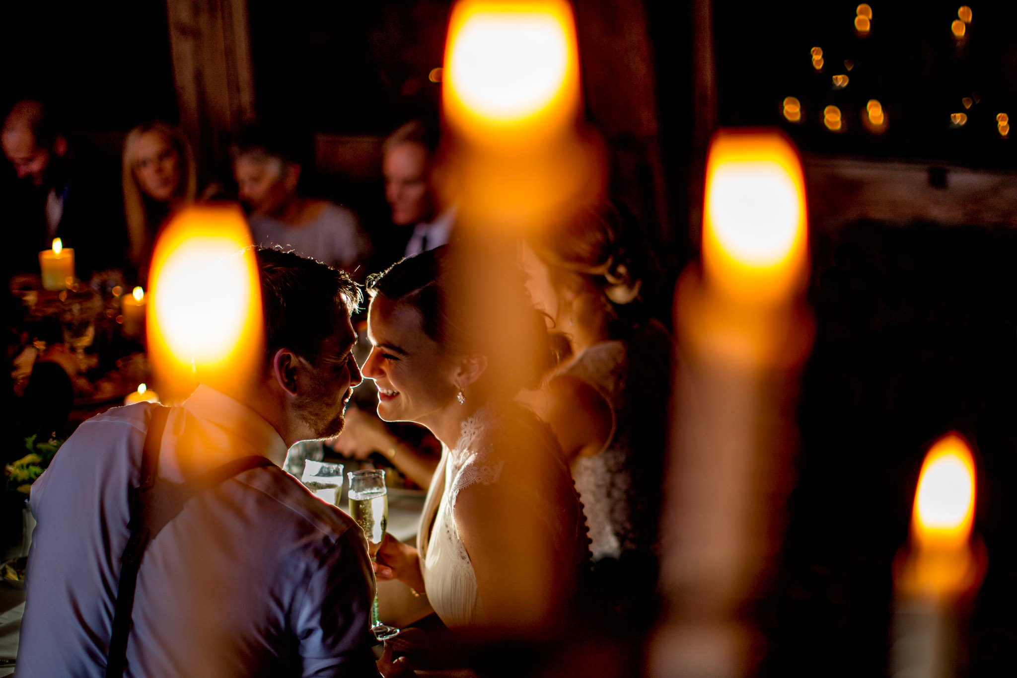 Bride and Groom smiling at reception through candle lights during reception at Silcox Hut at Timberline Lodge