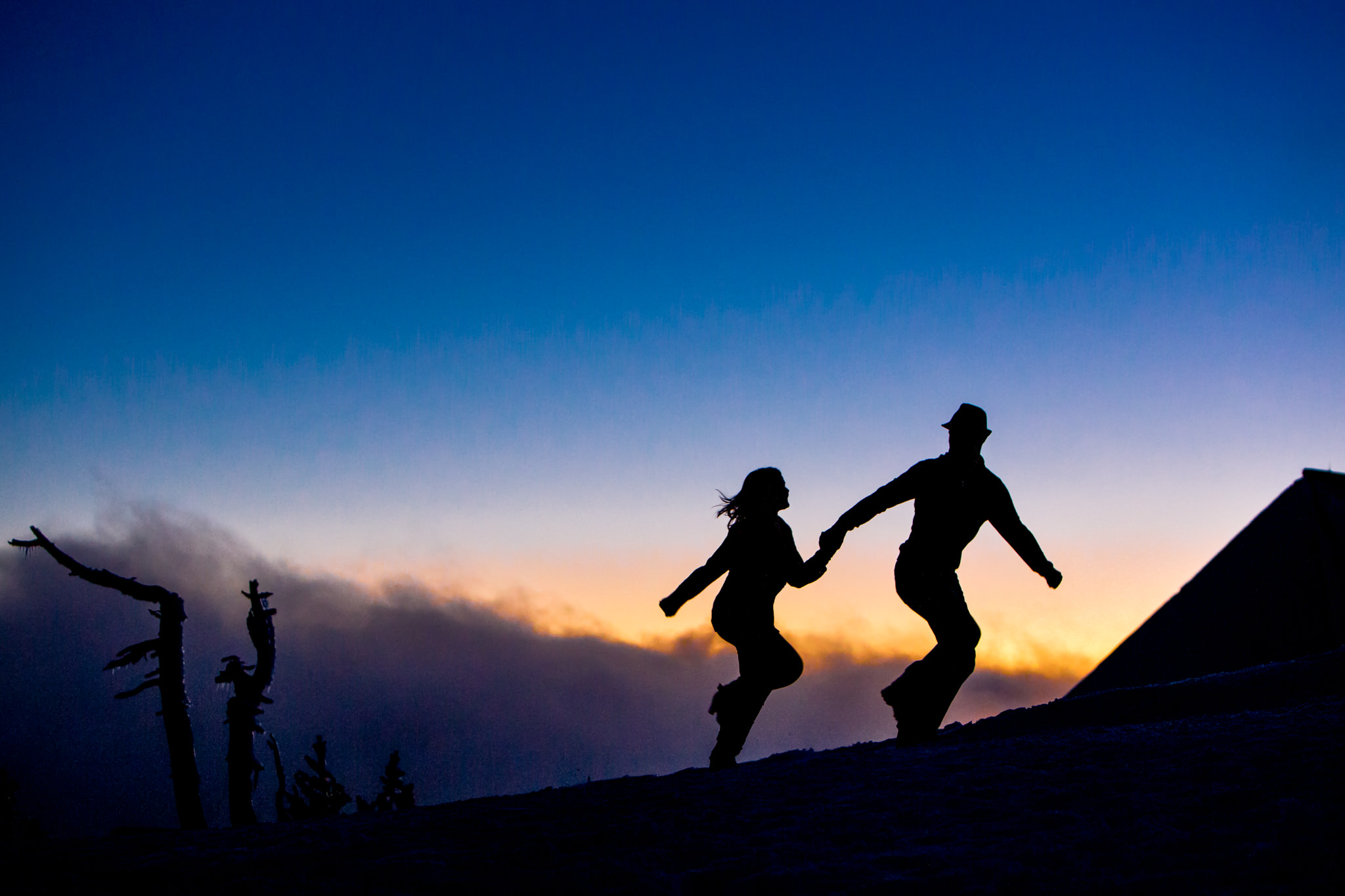 Engagement Photo of couple running up hill silhouetted at Timberline Lodge