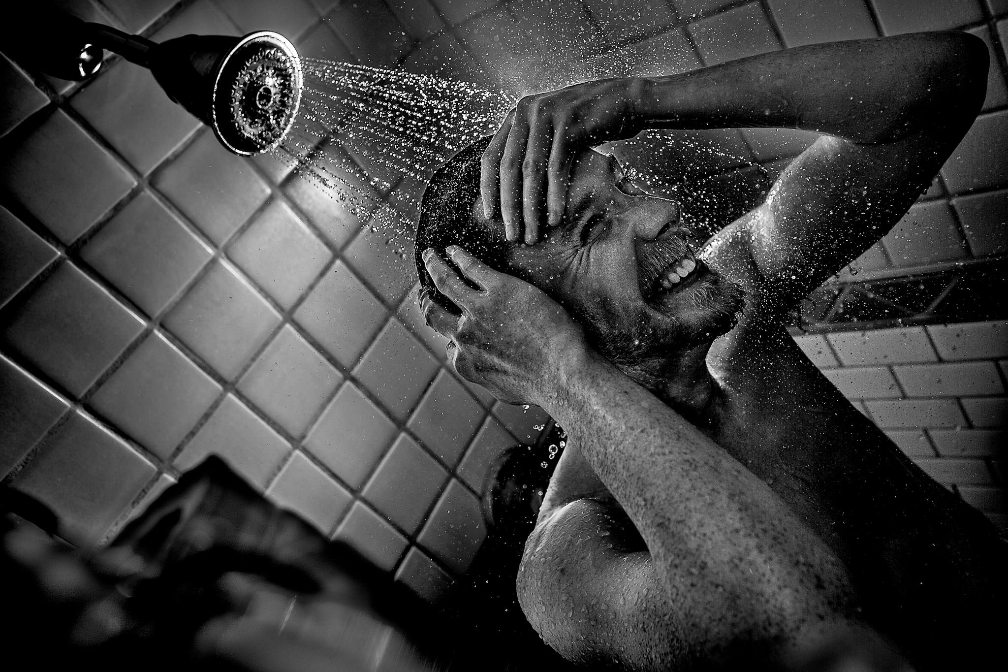 Groom getting ready with splashes under the shower head at Timberline Lodge