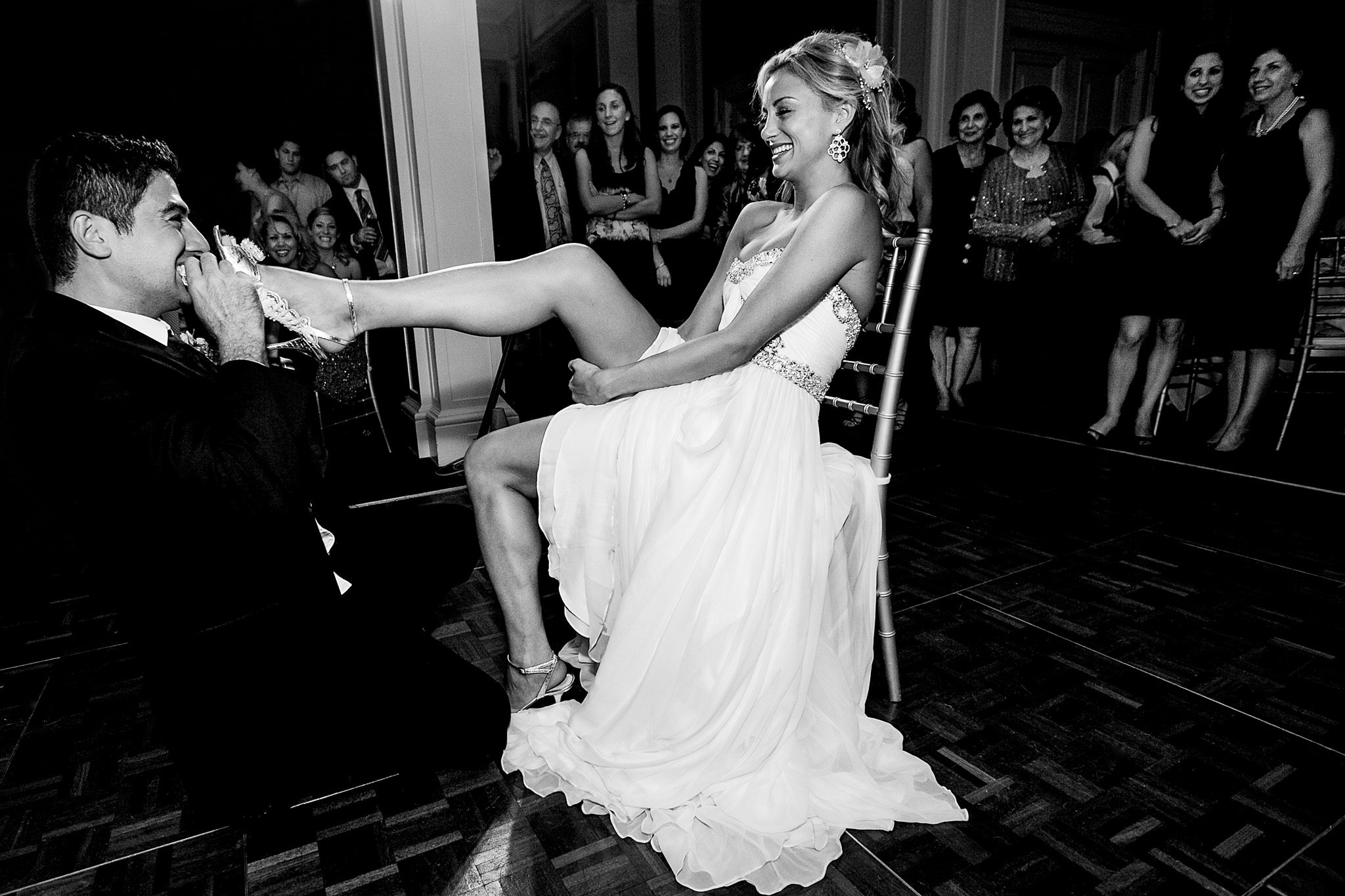 Bride on dance floor with groom retrieving garder at Waverly Country Club Portland oregon