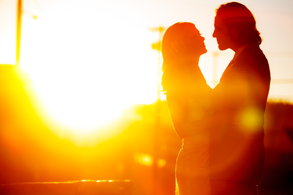 beautiful couple bathed in warm sunset light casting silhouettes and shadows from the low light.