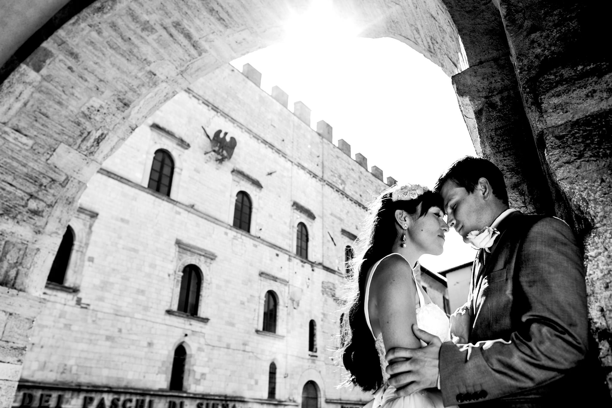Bride and groom embracing under arched doorway in Todi Italy Umbria