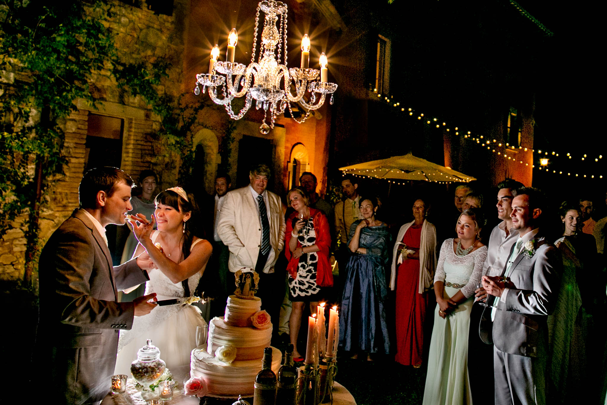 Bride feeding groom cake at reception under chandelier at Villa Tre Grazie in Todi Italy in Umbria