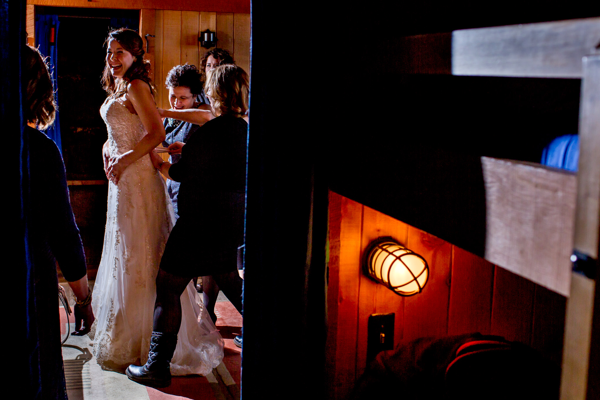 Bride getting dress on at Silcox Hut atop Timberline Lodge with friends and mother