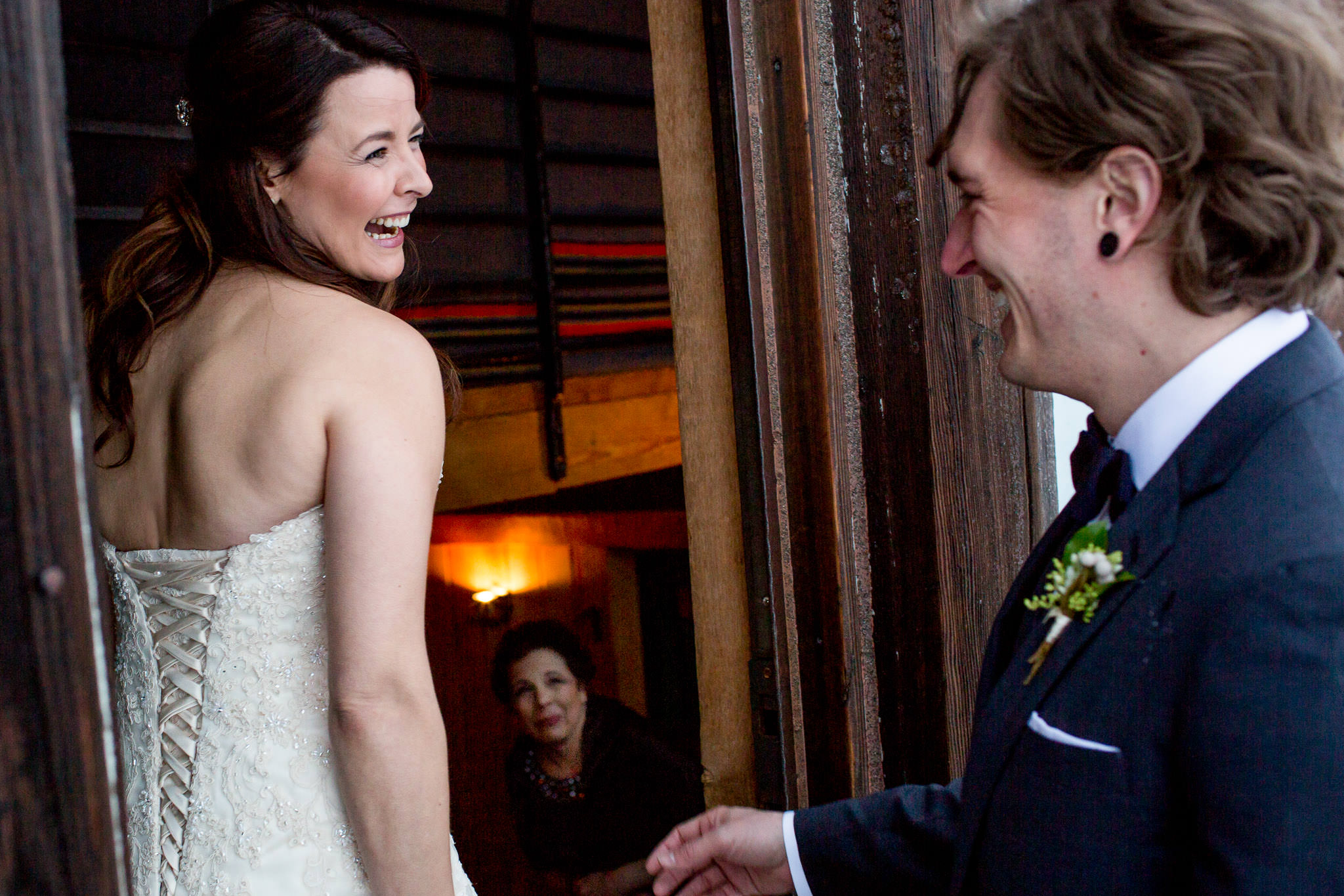 Bride seeing groom first time with emotional laughter and tears with mother in background at Silcox Hut