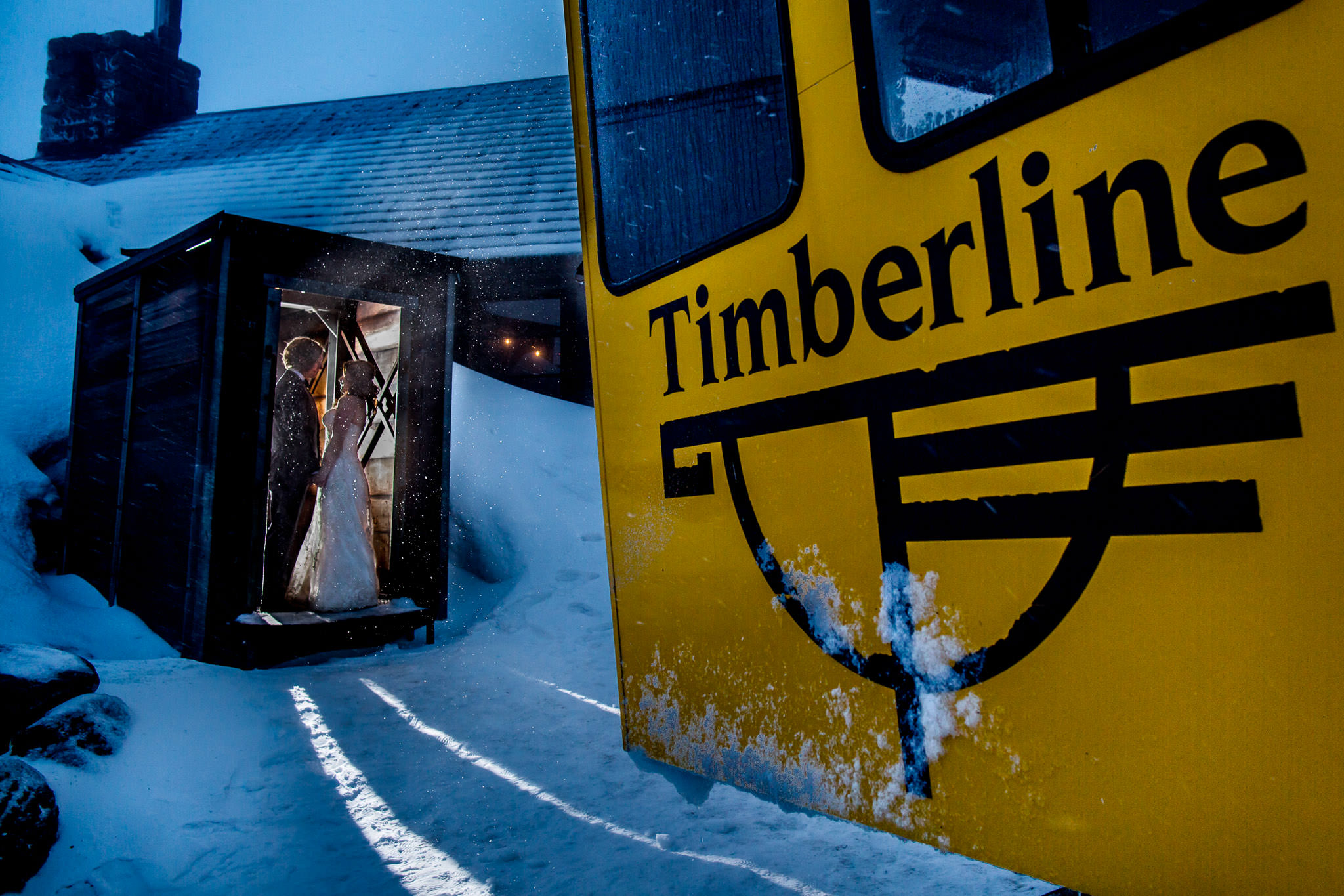 Bride and Groom standing in entrance to Silcox Hut with snow cat in foreground