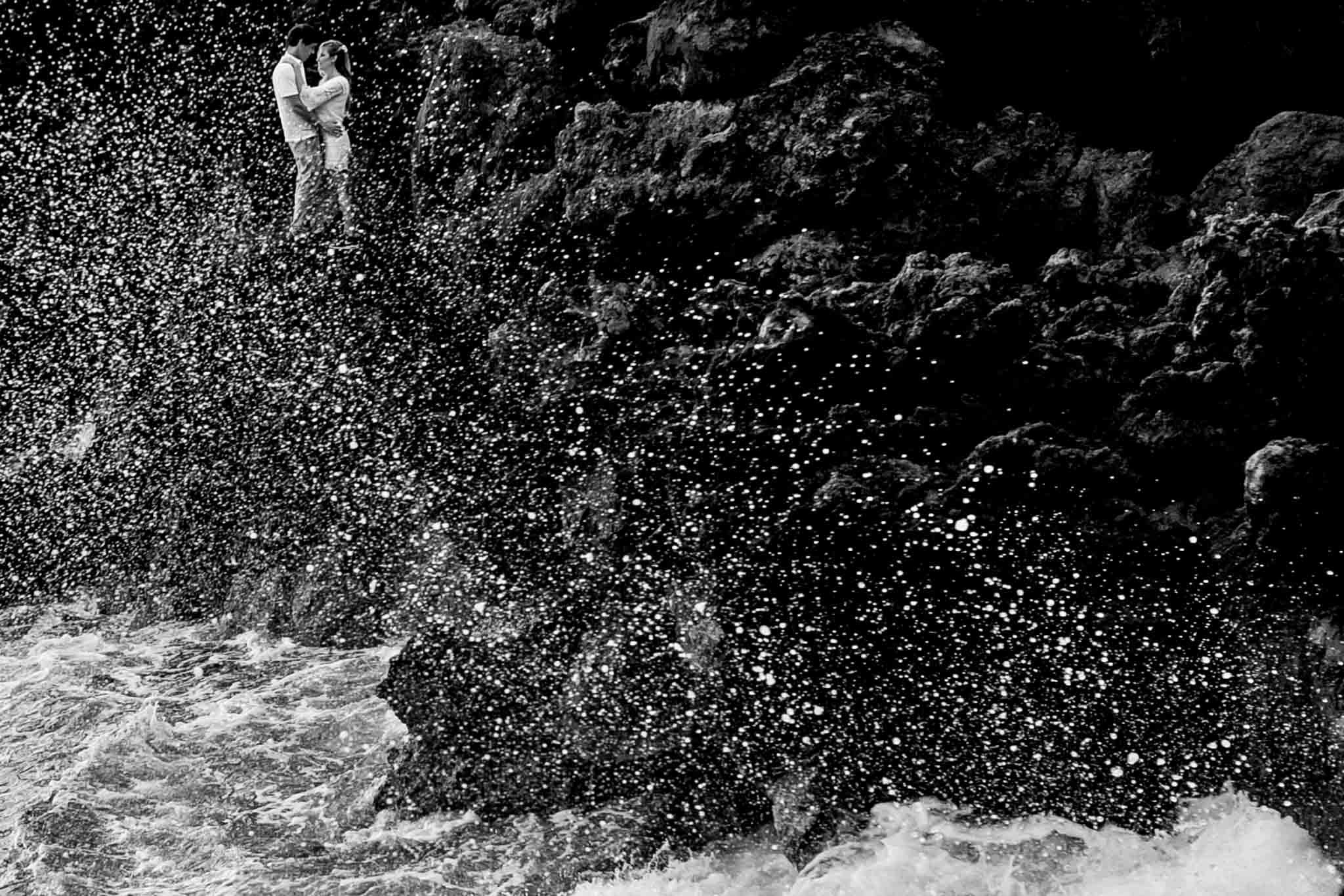 Ocean spraying over foreground of engagement couple along lava cliffs near Kona Hawaii