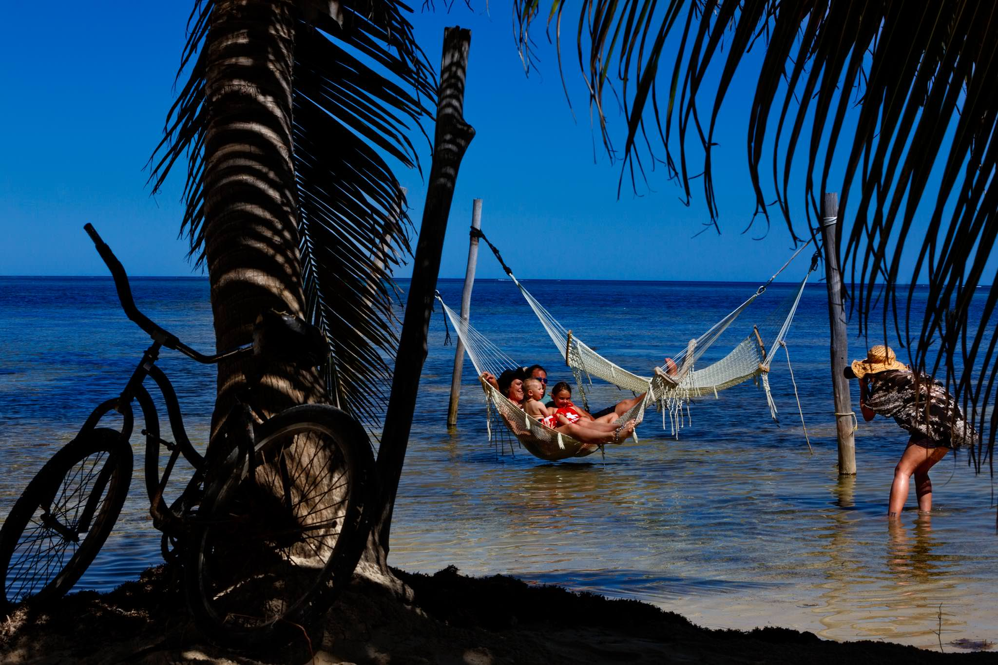 Photographer shooting in water in Belize with family in hammock