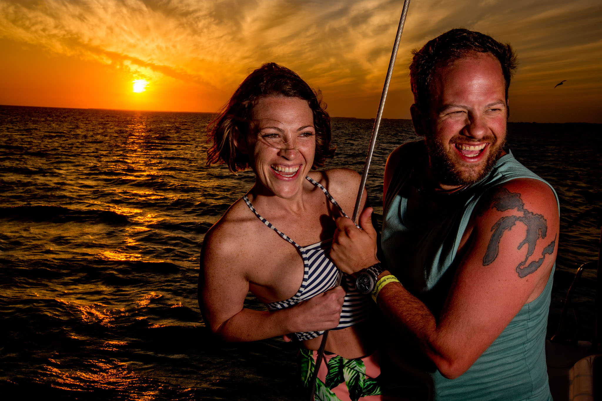 Bride and Groom to be at golden sunset on catamaran in Belize for brides birthday cruise day before wedding at Portofino Beach Resort