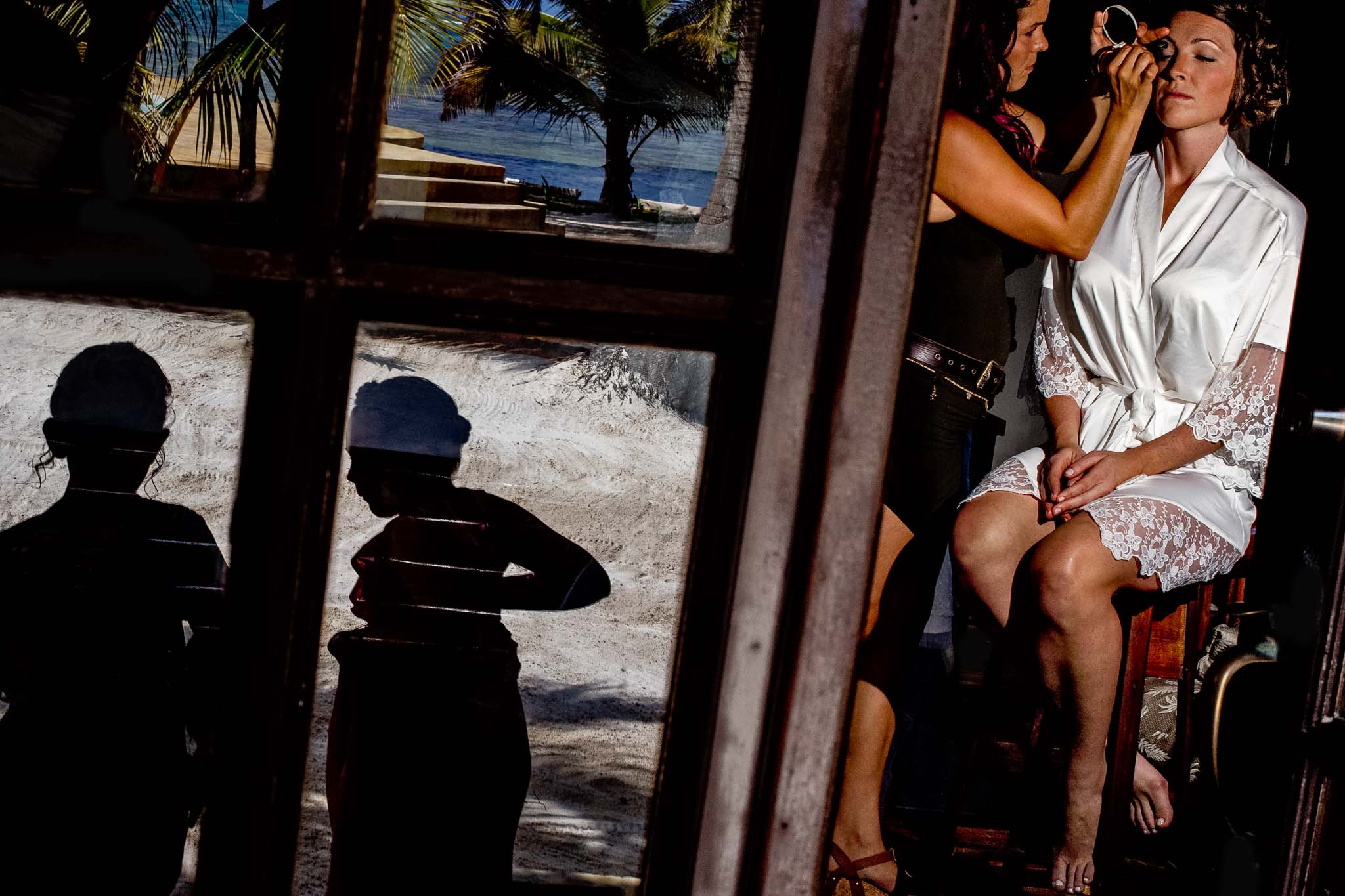 Bride Getting Ready through window with kids silhouetted at Portofino Beach Resort in Belize