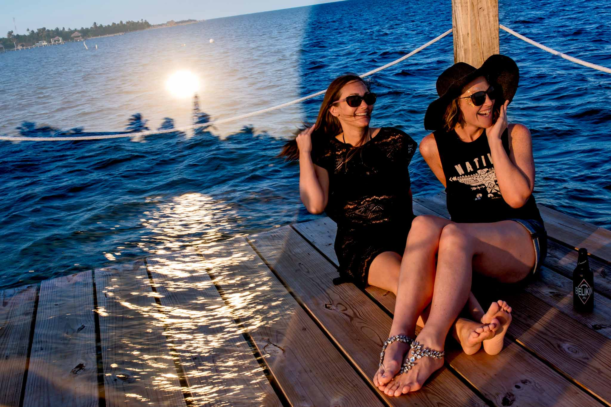 Bride and sister sitting on a dock at sunset with reflections at Belize wedding