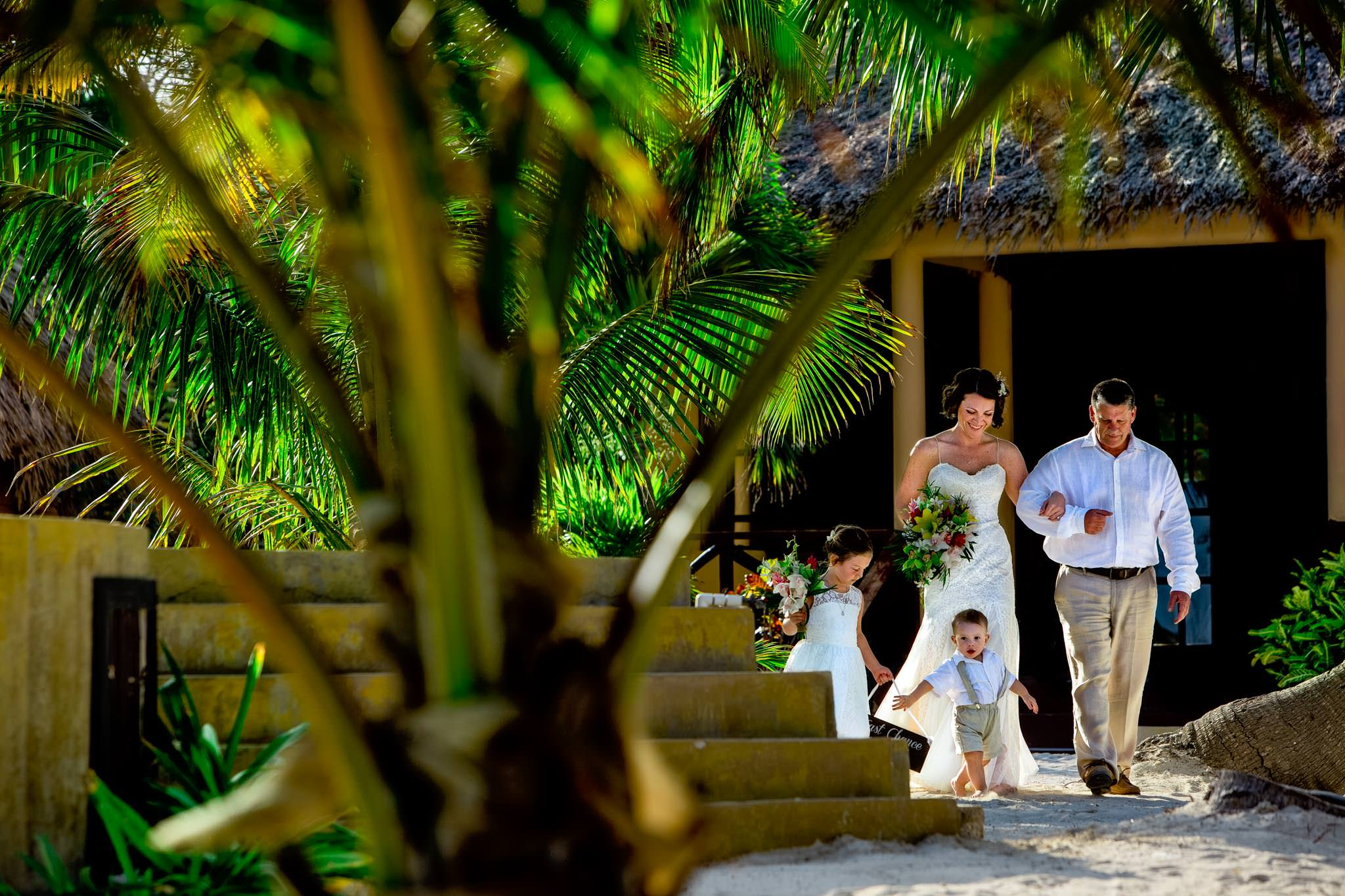 Bride walking into ceremony with children and father in Portofino Beach Resort in Belize