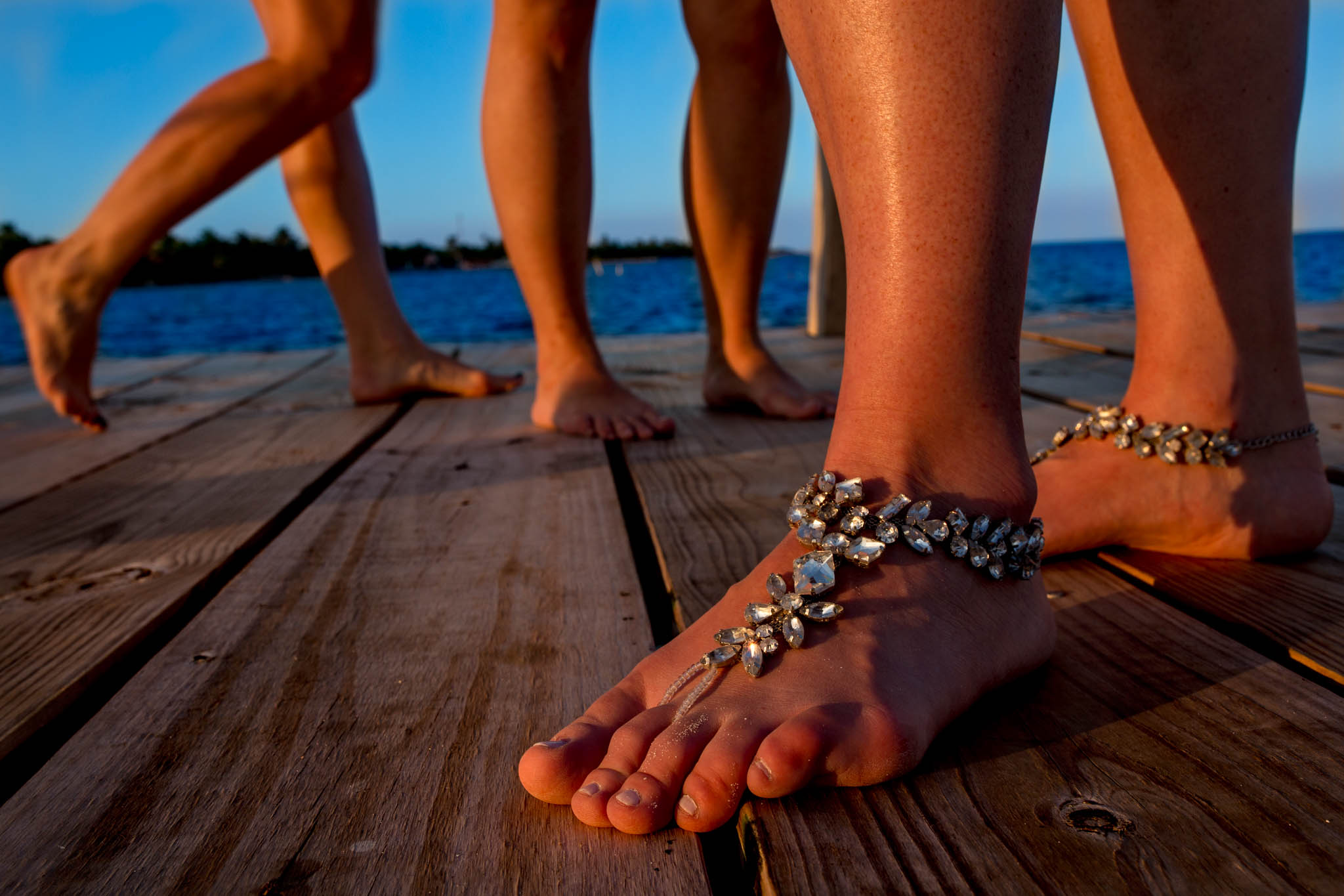 Brides feet with bridesmaids feet on dock in Belize over ocean