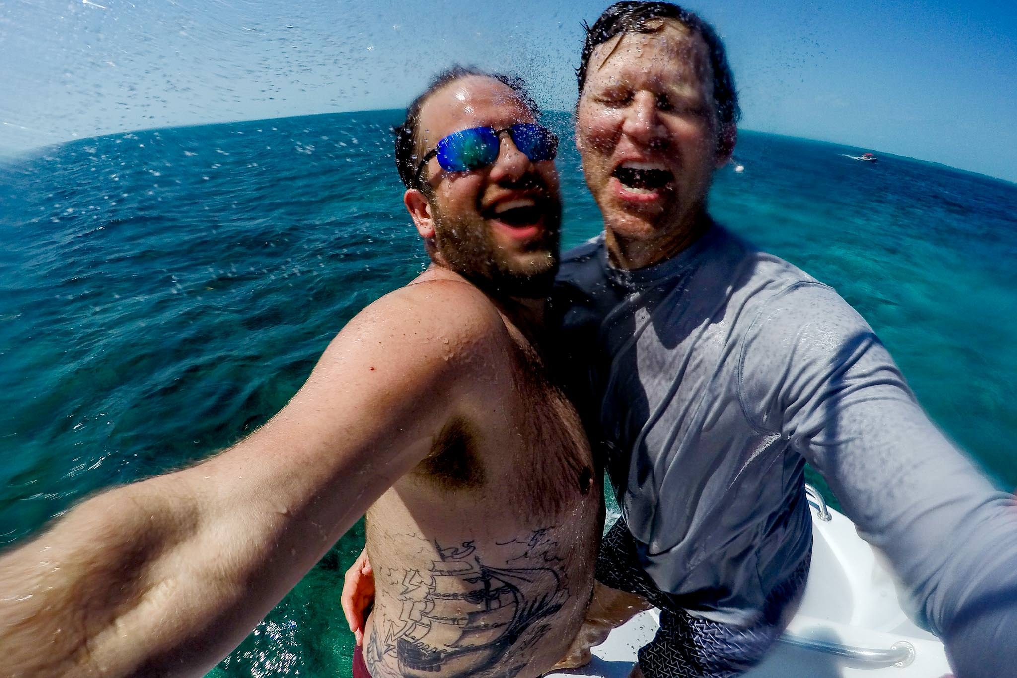 Photographer and Groom being hosed off on back of Catamaran in Belize day before wedding at Portofino Beach Resort