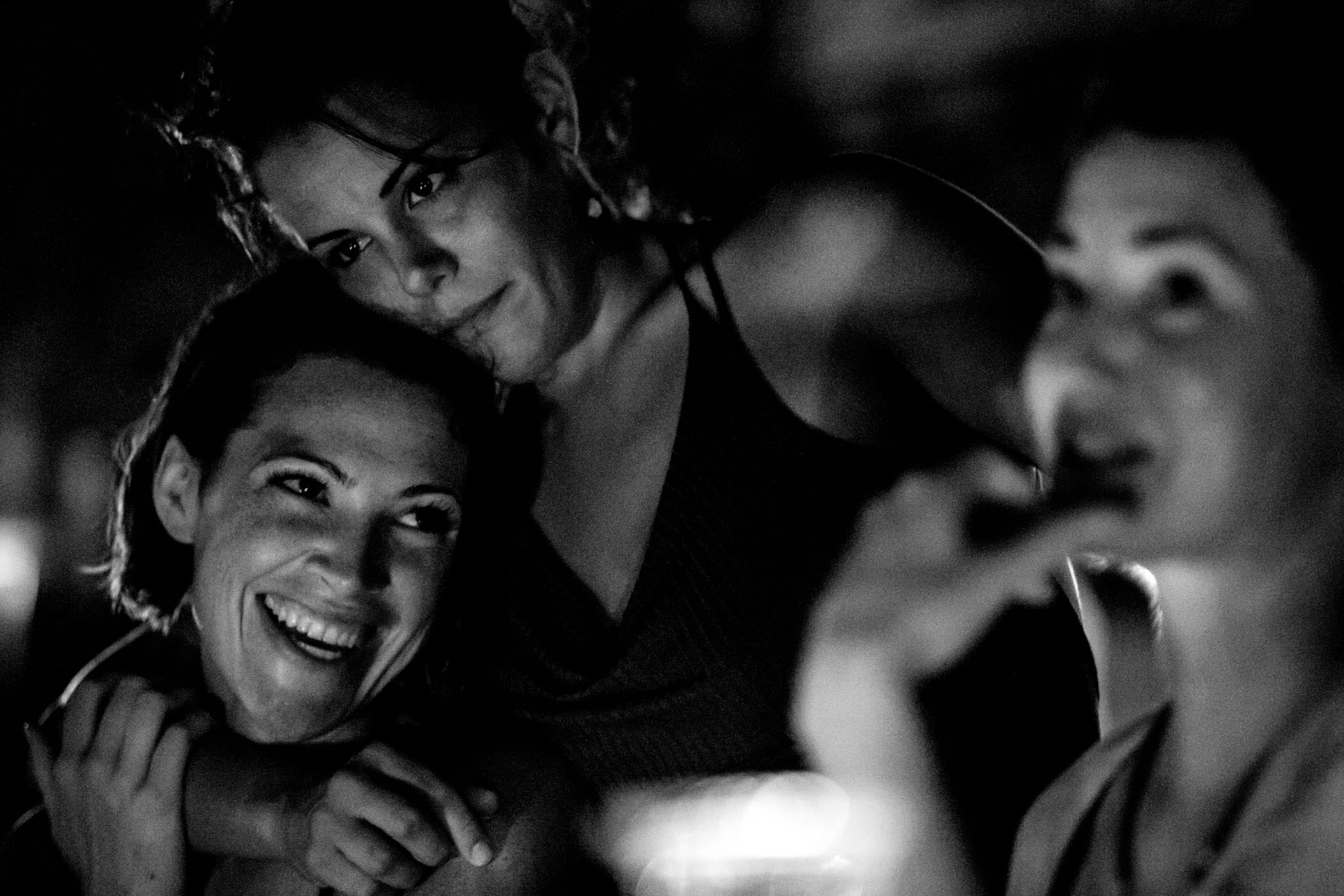 Bride laughing with friends over dinner night before Belize wedding at Portofino Beach Resort