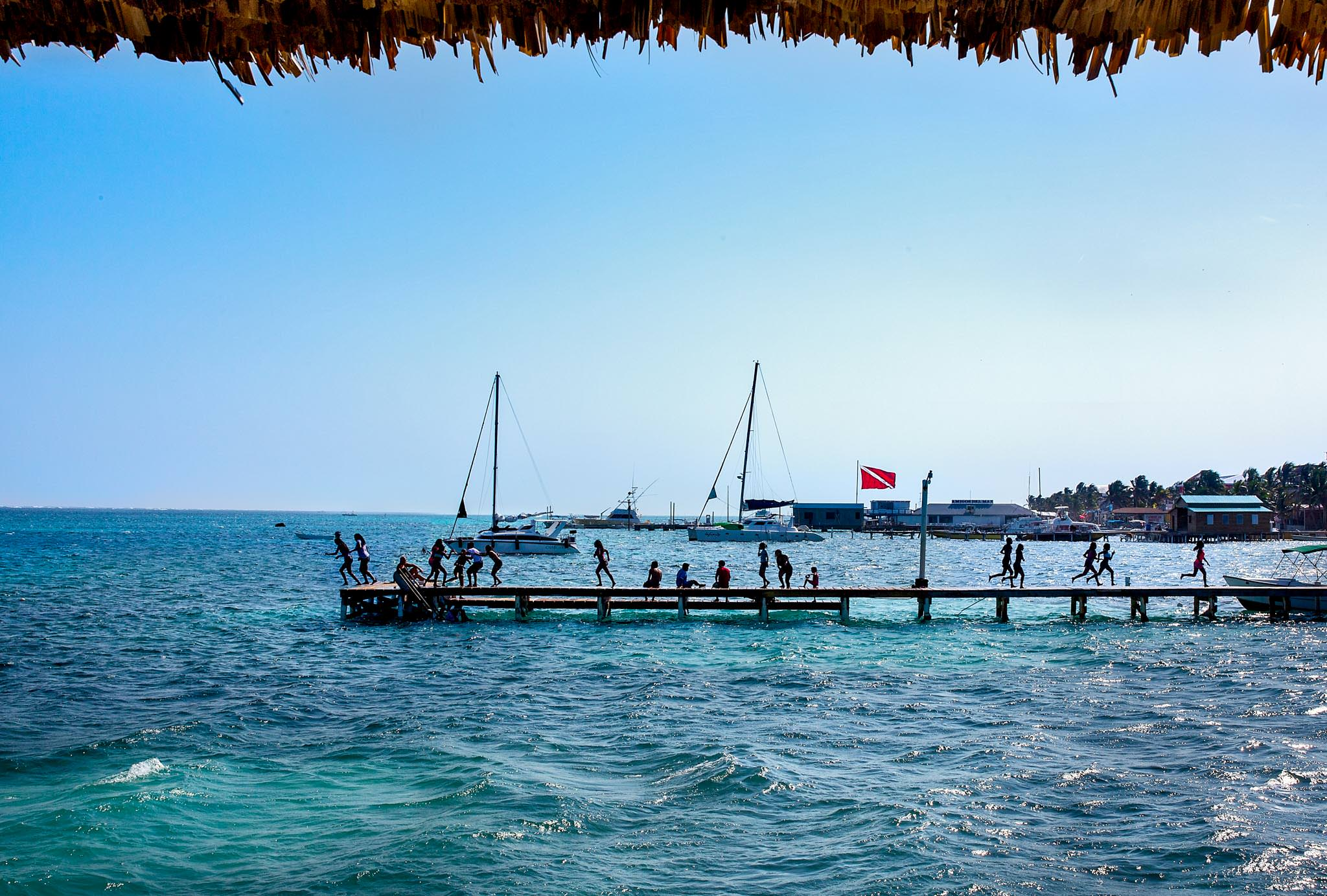 Silhouette of children running on dock in Belize before wedding day