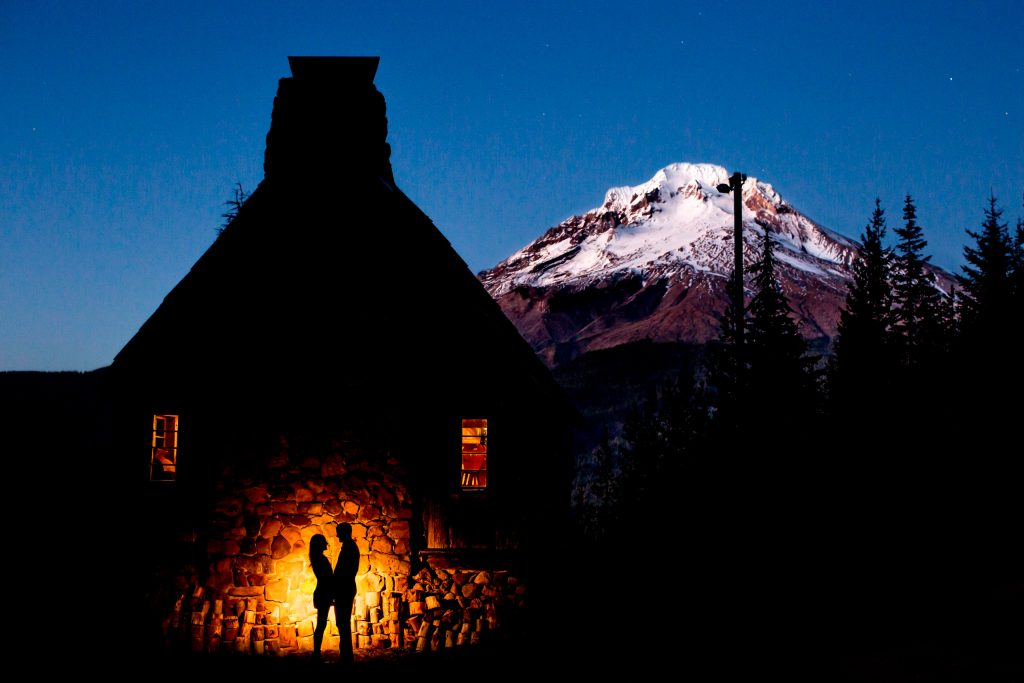 Engagement photo silhouette of couple against lodge with Mt Hood in distance
