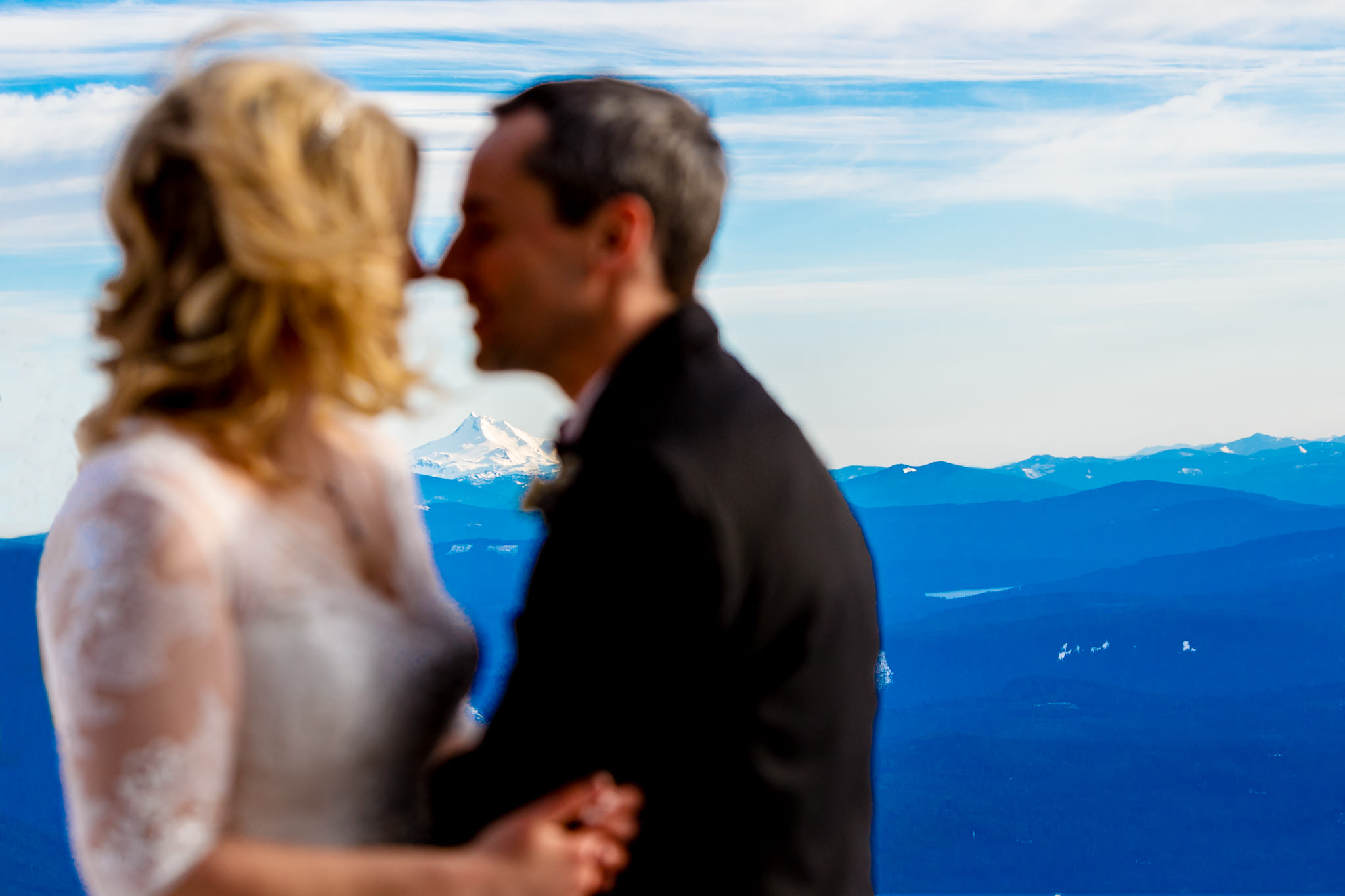 Bride and groom embracing with Mt Jefferson in distance atop Mt Hood near Silcox Hut