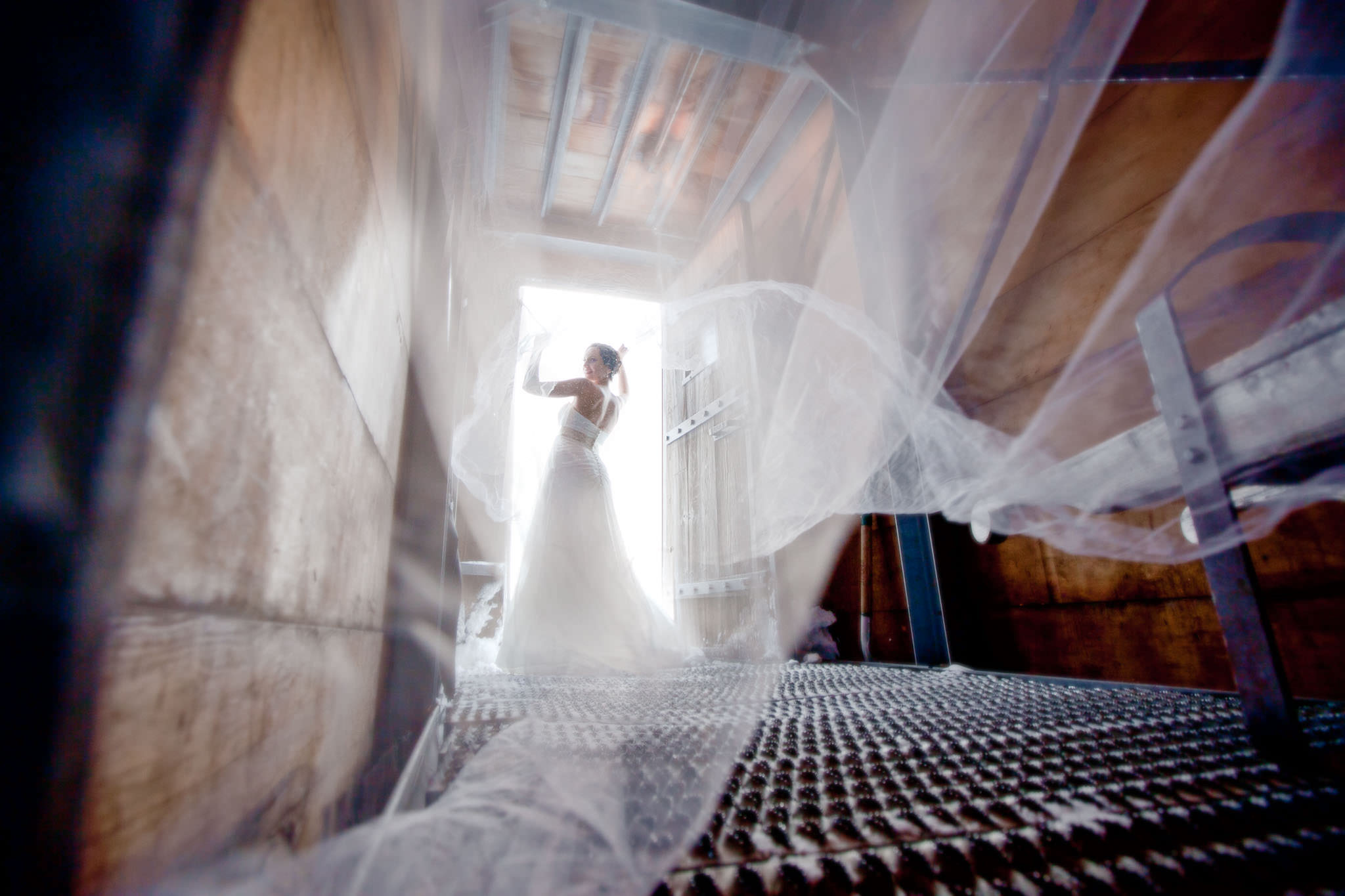 Bride in doorway leading into Silcox Hut with flying veil