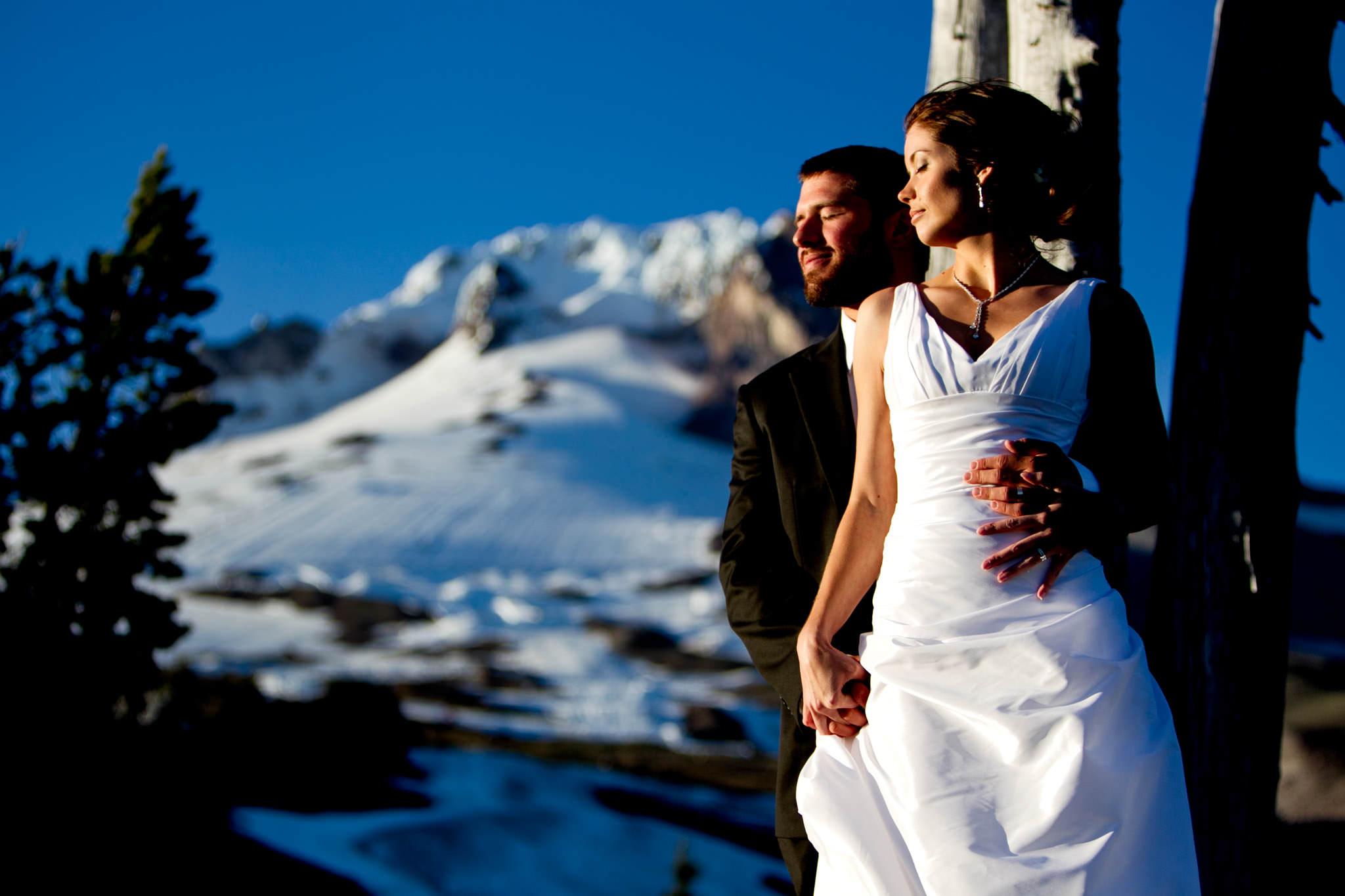 Golden sunset on bride and grooms faces atop Mt Hood above Timberline Lodge
