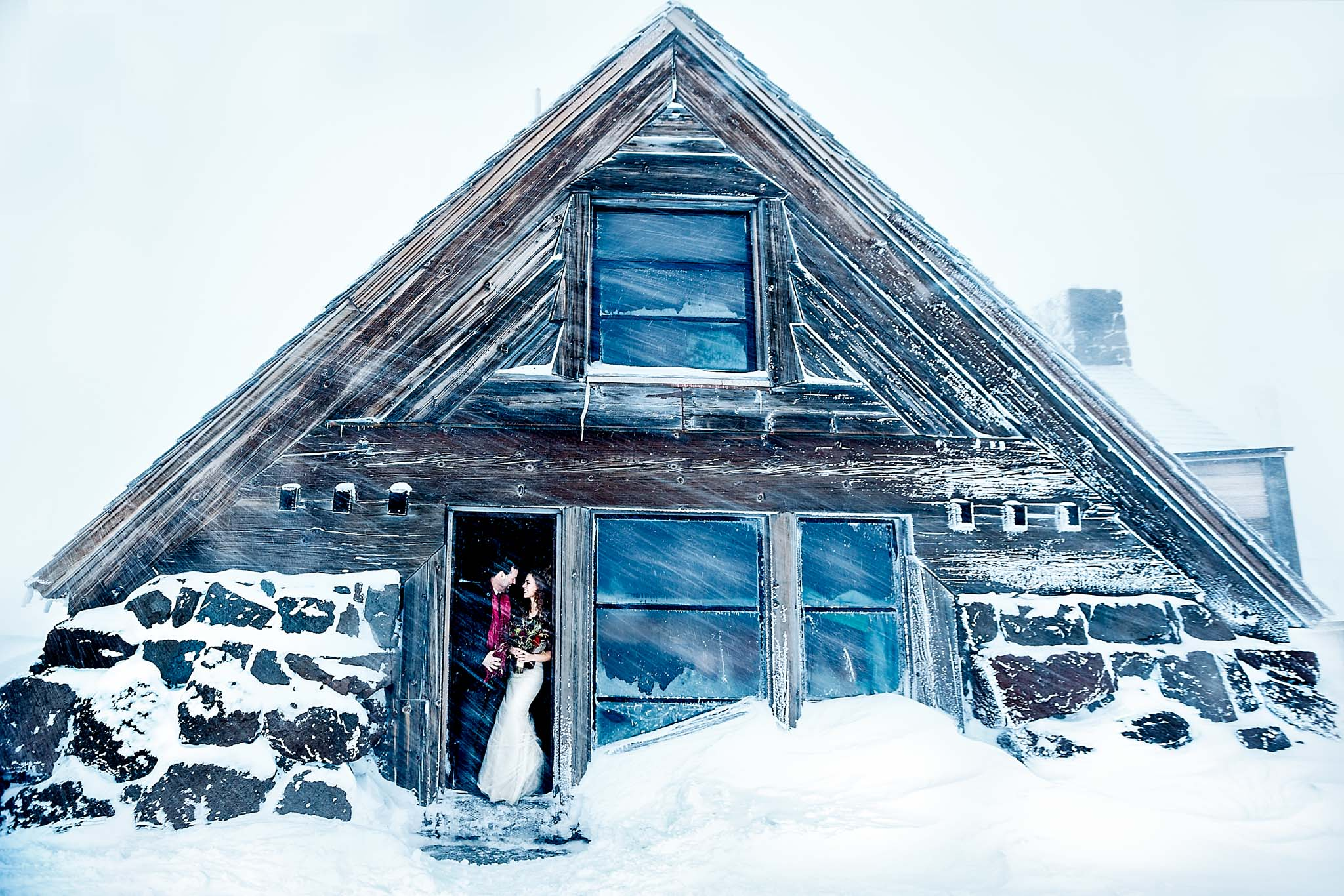 Bride and Groom standing in doorway at Silcox Hut amidst snow flurry