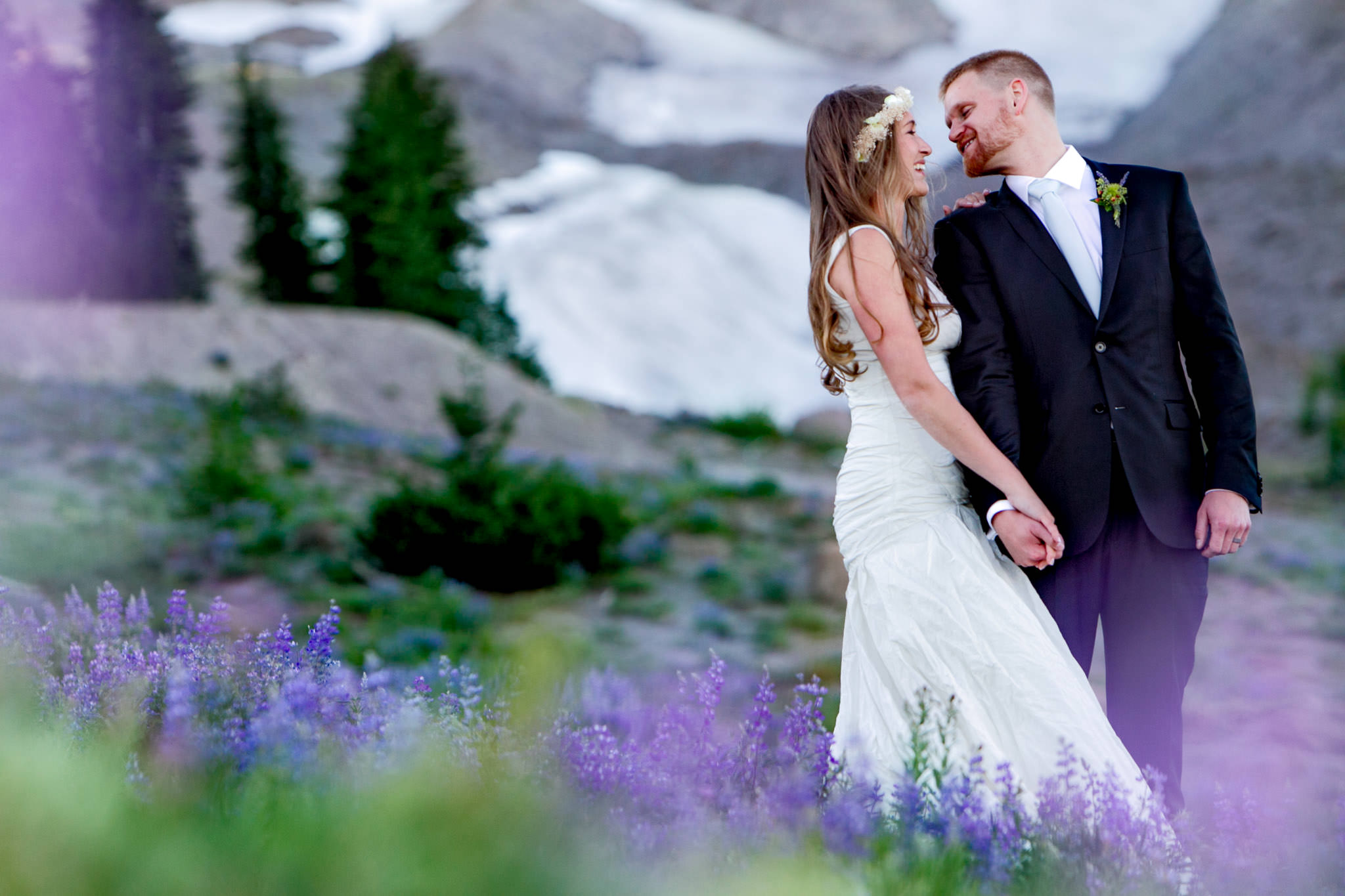 Bride and Groom laughing in purple flowers atop Mt Hood just above Timberline Lodge for their summer wedding