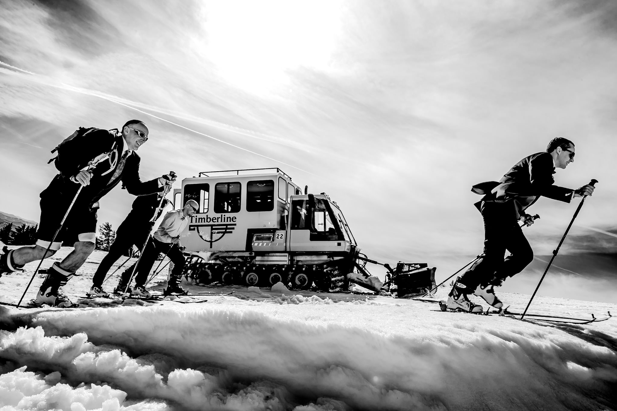 Groomsmen race skiing up Timberline with snow cat