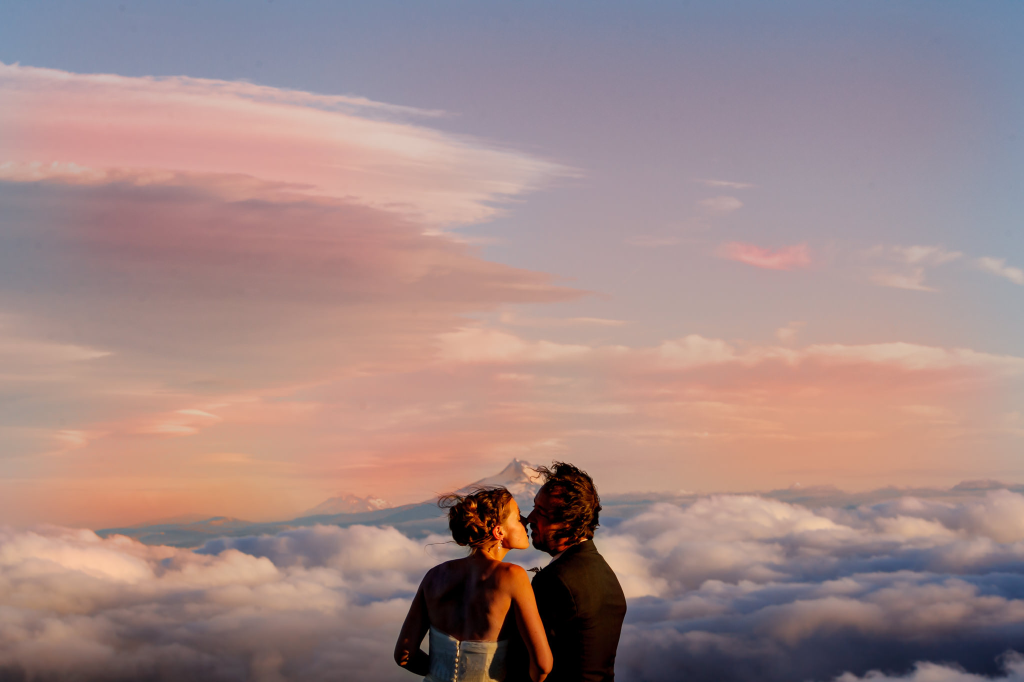 Bride and groom at sunset atop Mt Hood at Silcox Hut above Timberline Lodge