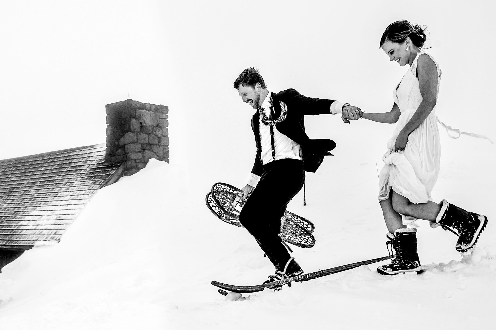 Bride and Groom running in old wooden snow shoes down the mountain outside Silcox Hut atop Mt Hood at Timberline Lodge