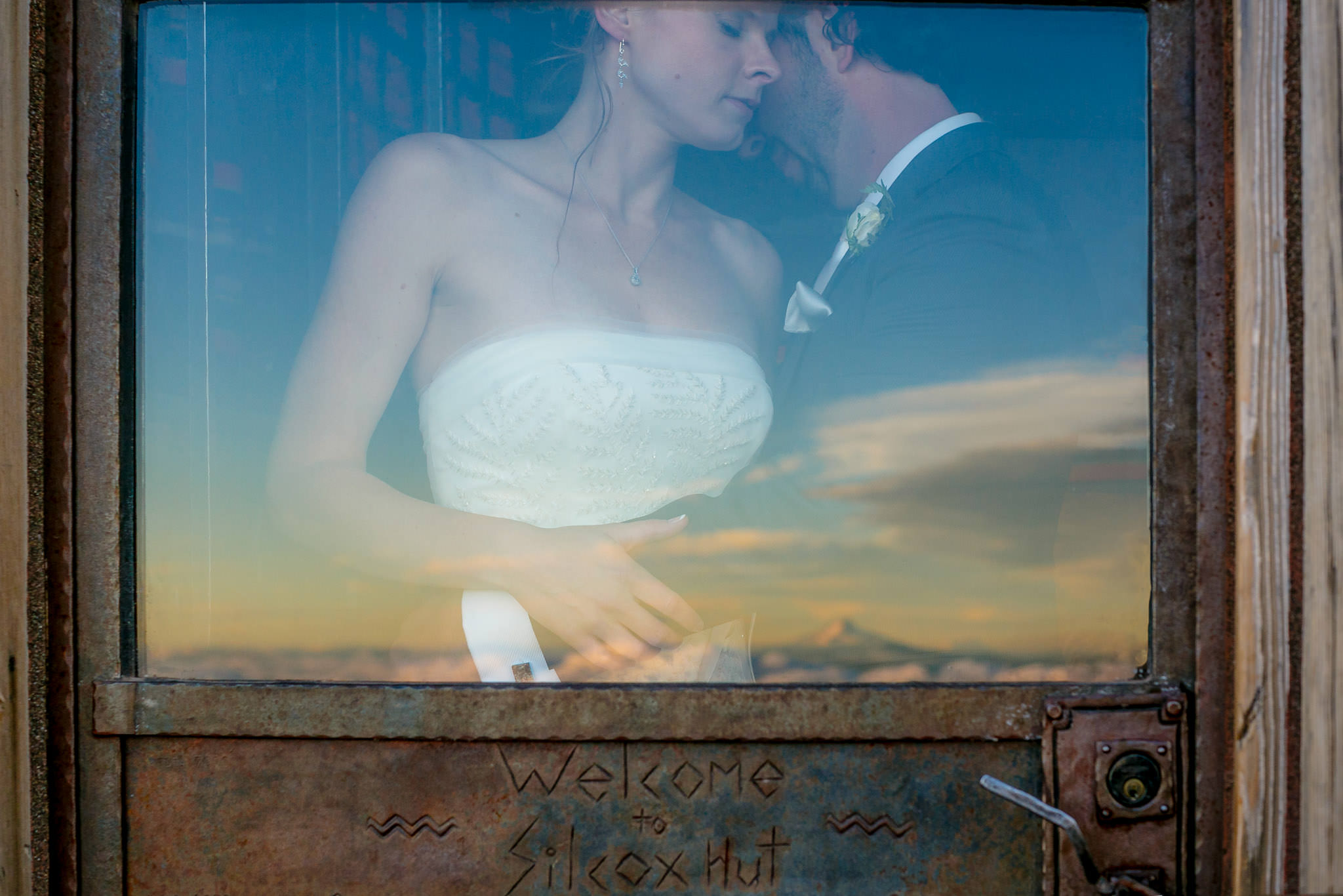 Bride and Groom reflected in Silcox Hut window with Mt Hood