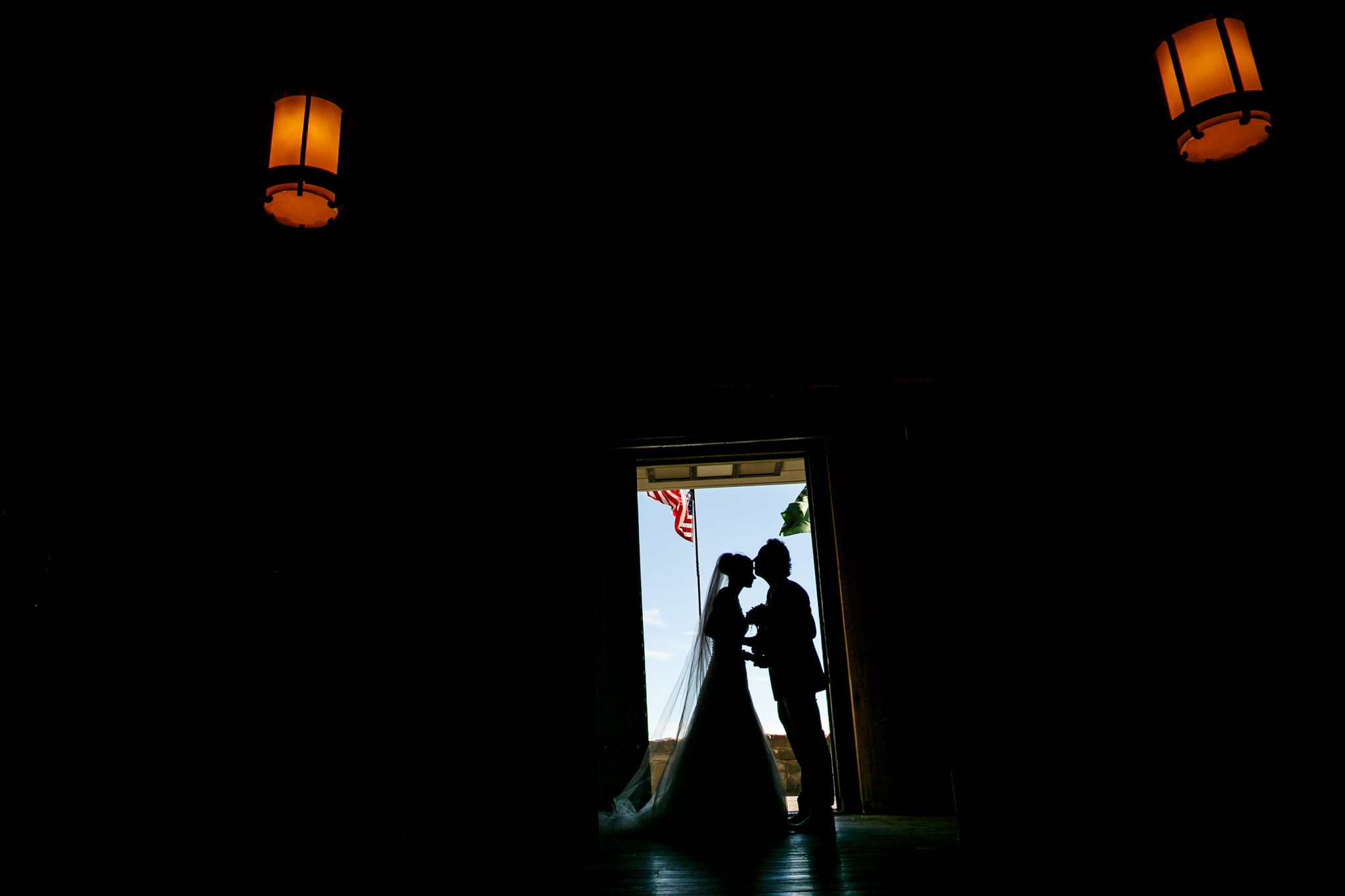 Bride and Groom silhouetted in doorway in Timberline Lodge