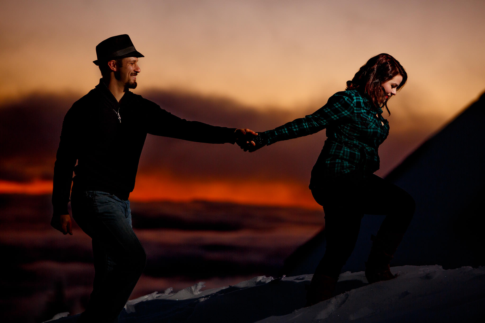 Engagement portrait of couple walking in red orange sunset atop Mt Hood at Timberline Lodge