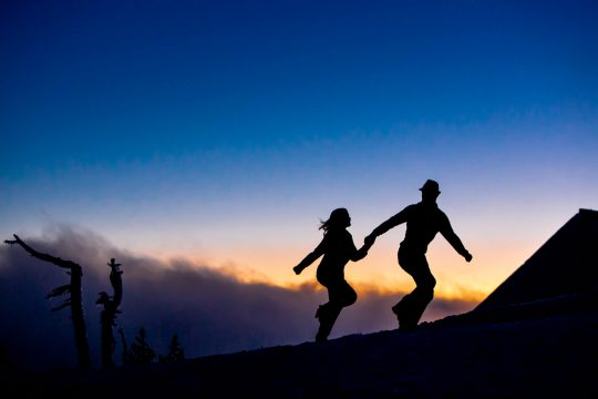 Epic engagement portrait of couple running silhouetted over sunset atop Mt Hood at Timberline Lodge