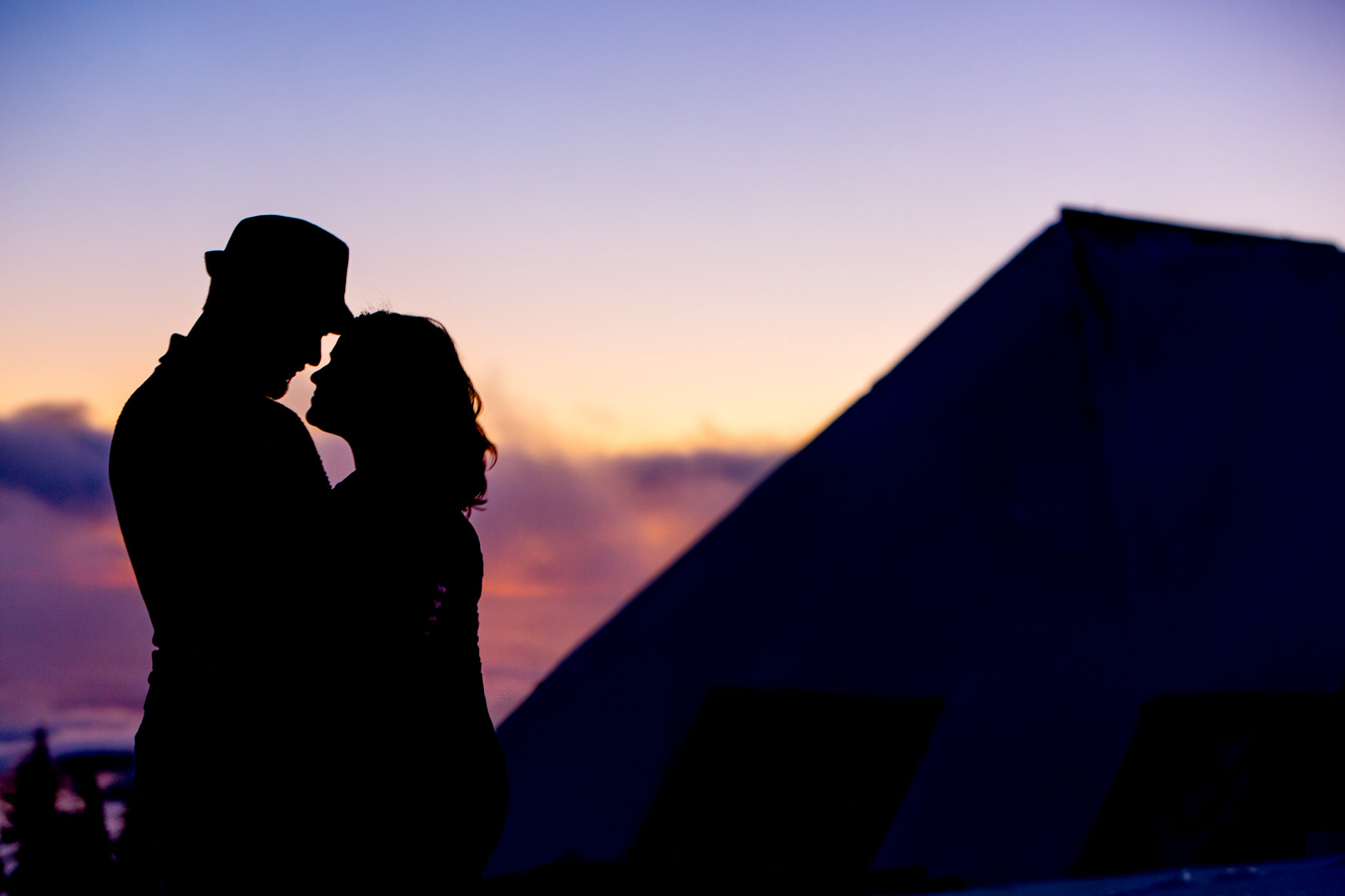 Engagement portrait of couple against pink sky atop Mt Hood at Timberline Lodge