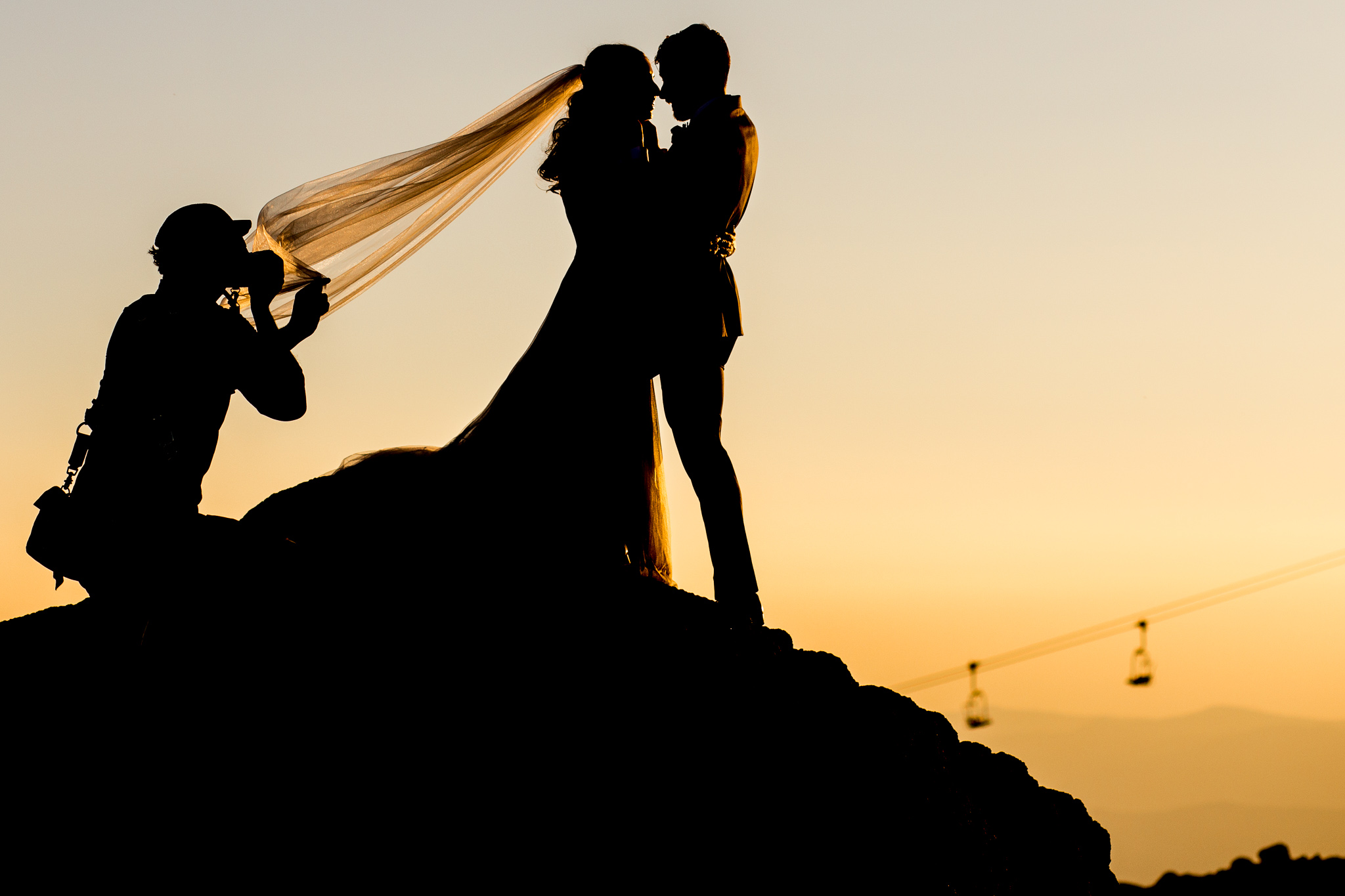 Photographer capturing bride and groom at golden hour in silhouettes