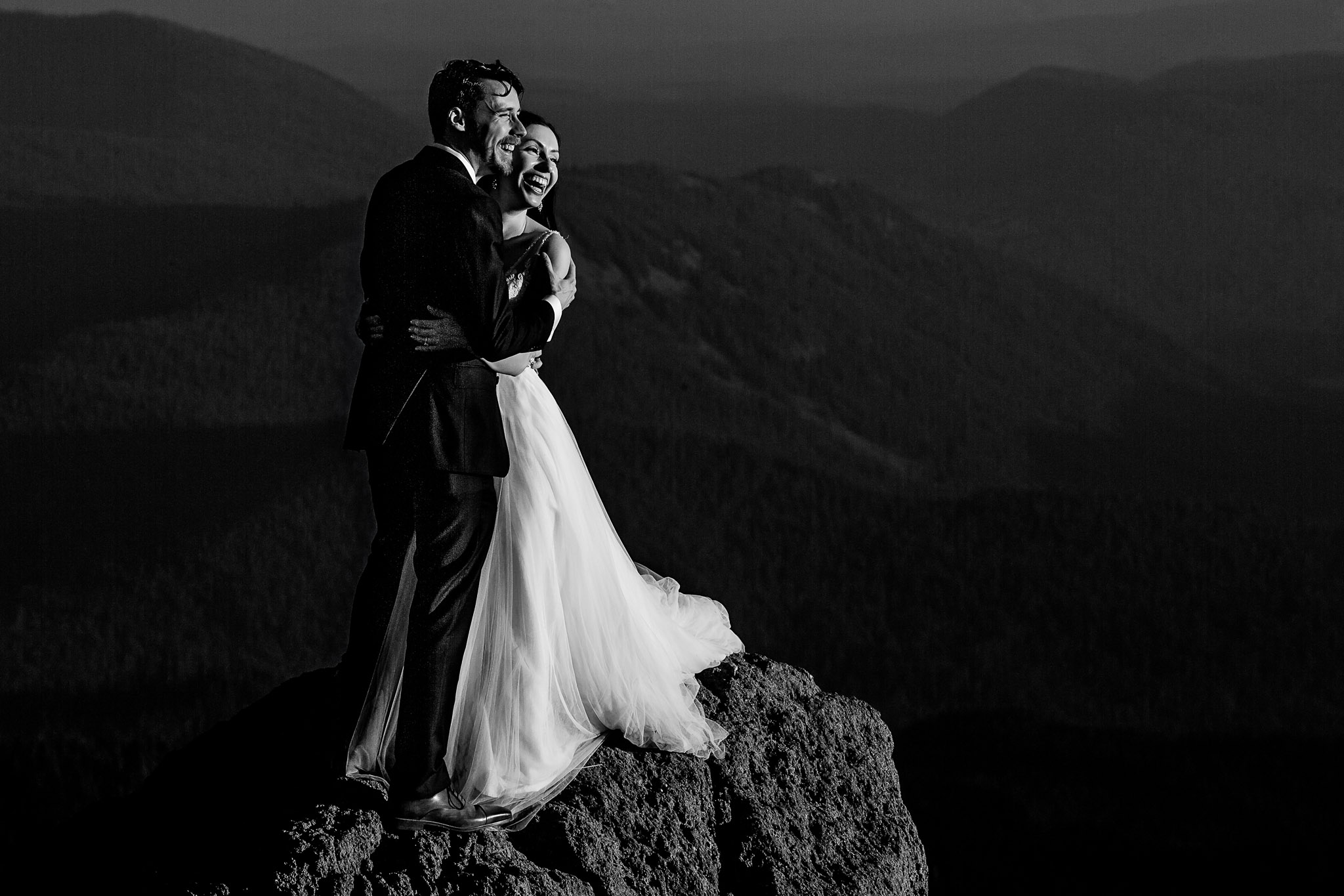 Bride and Groom atop Mt Hood on large boulder looking out over valley