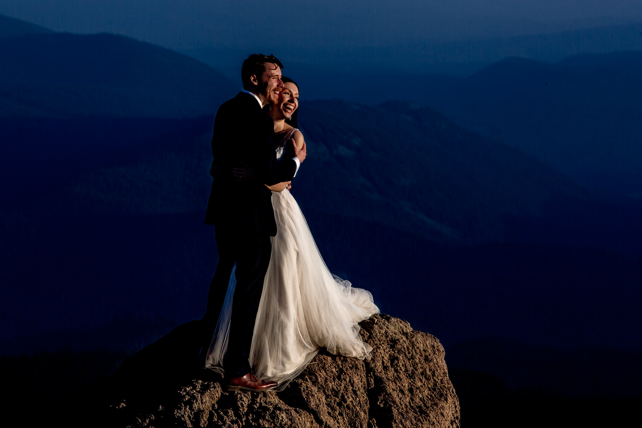 Bride and Groom looking over valley on rock atop Mt Hood above Timberline Lodge