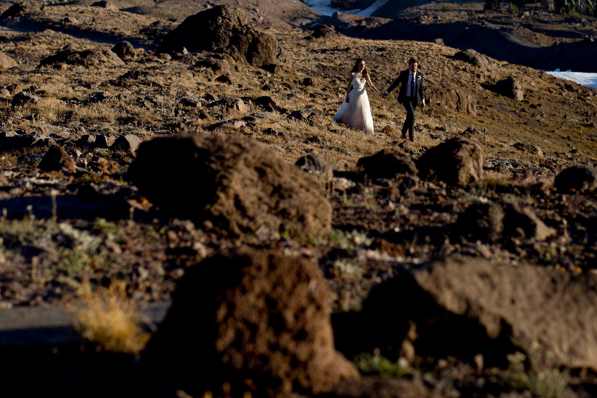Bride and groom walking on mountain during summer wedding atop Mt Hood above Timberline Lodge