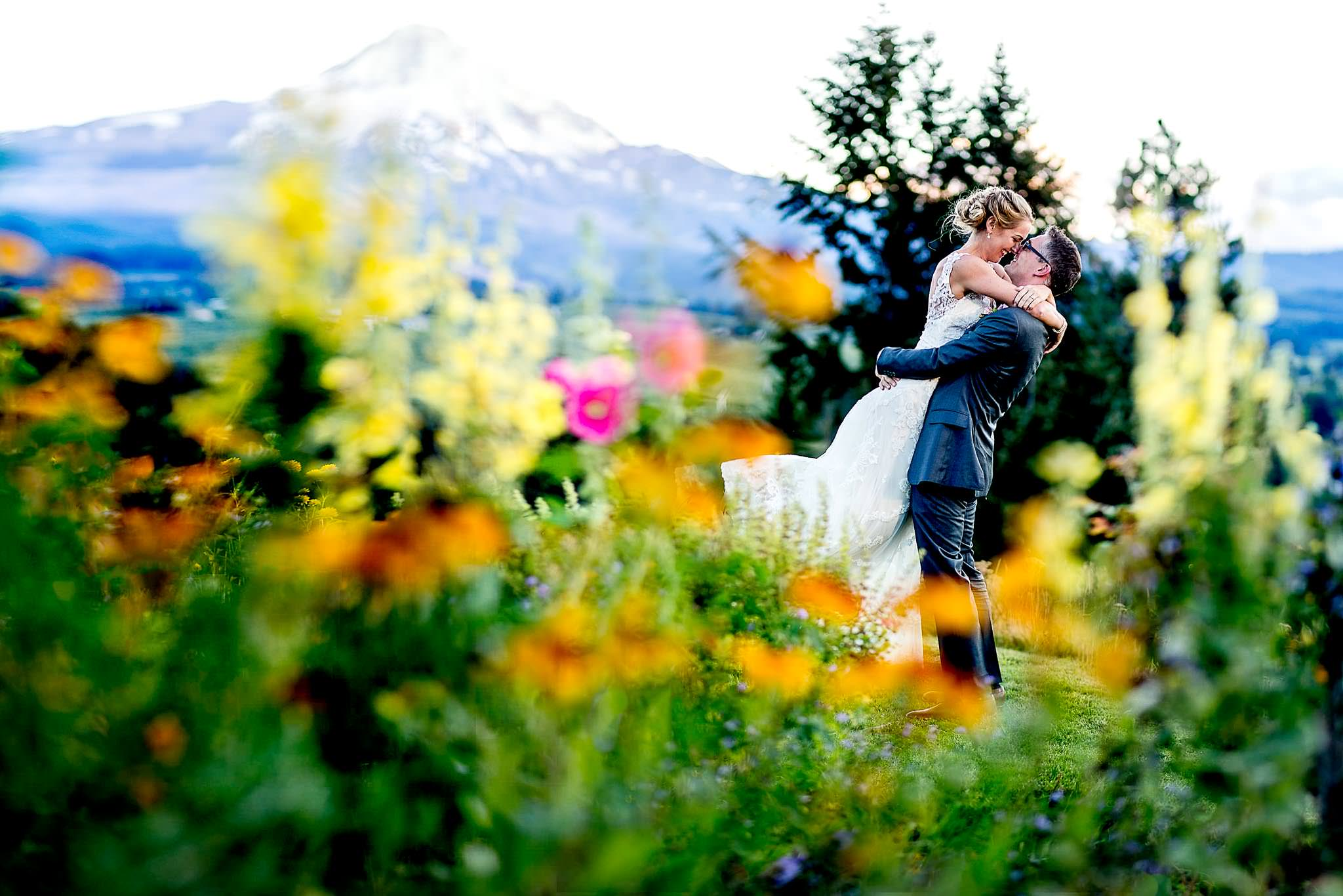 Bride and Groom embracing in flowers at Mt Hood Organic Farms with Mt Hood in distance