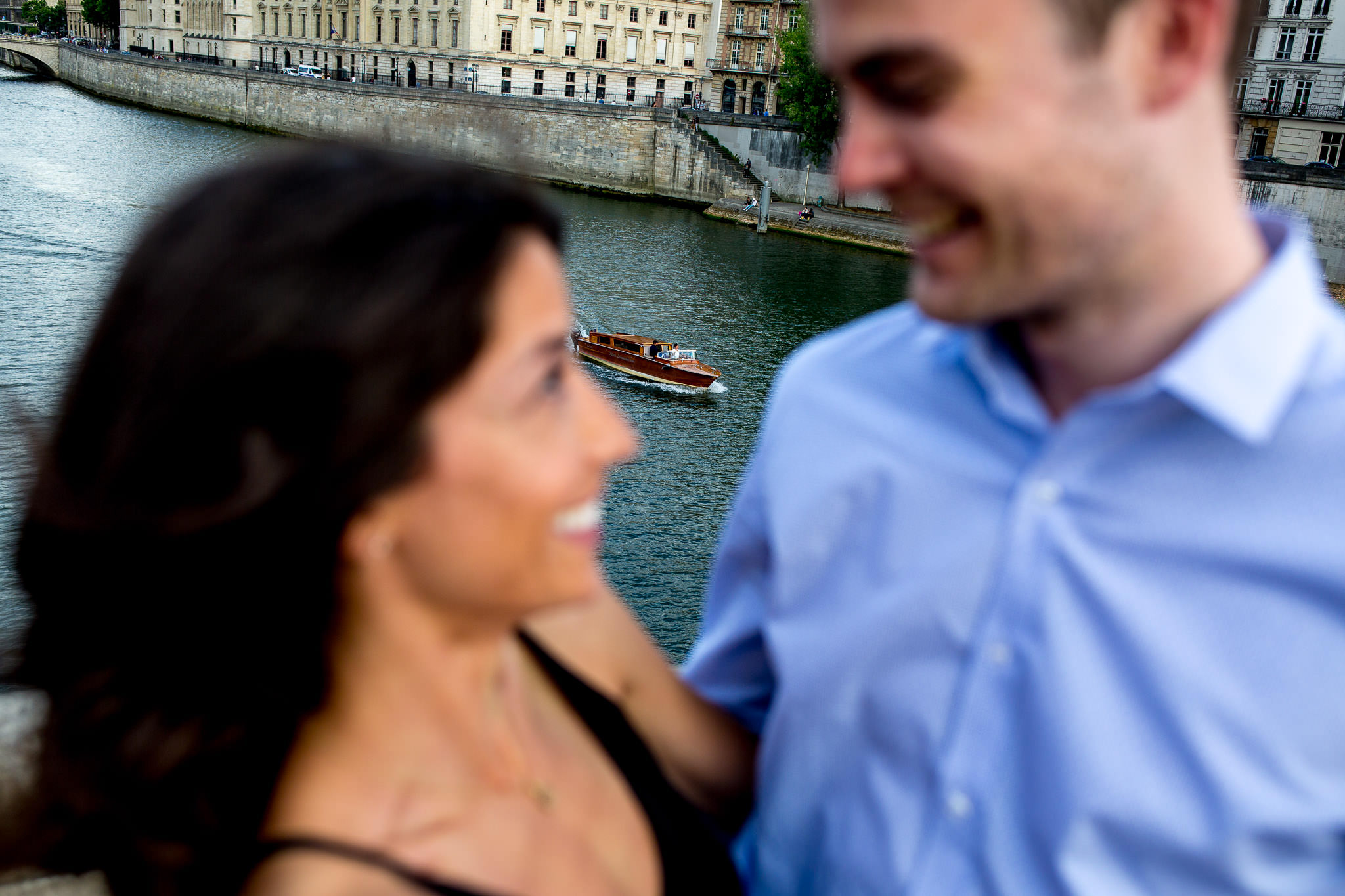 Engagement photo on oldest bridge in Paris France with boat in distance