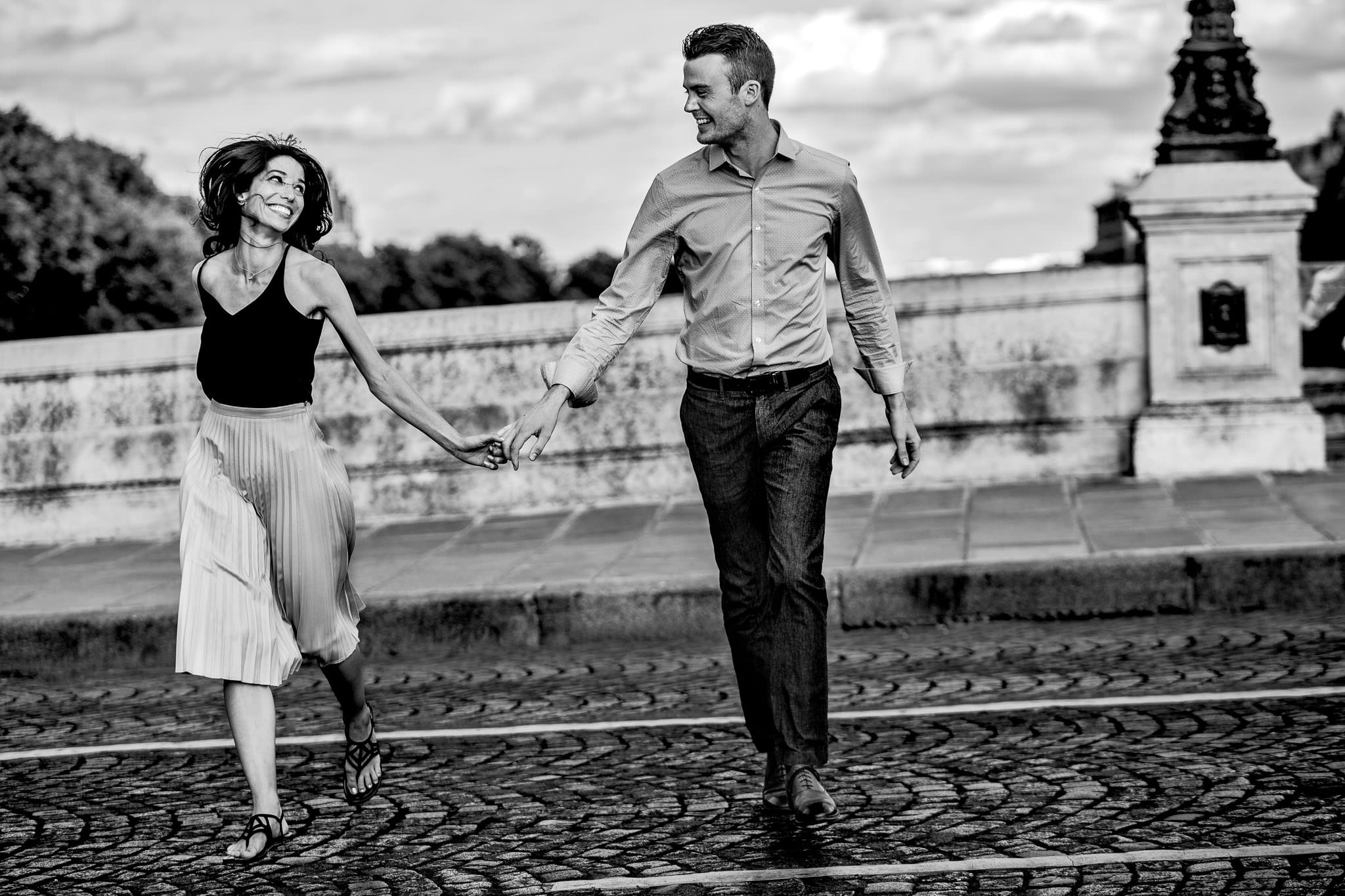 Engagement photo on oldest bridge in Paris France while running across cobble stones